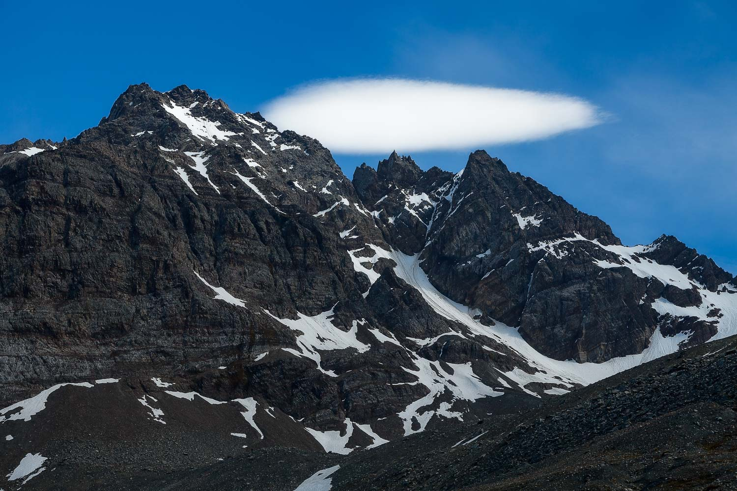 A spectacular view of a low lying cloud hovering over mountain peaks on  South Georgia, Antarctica