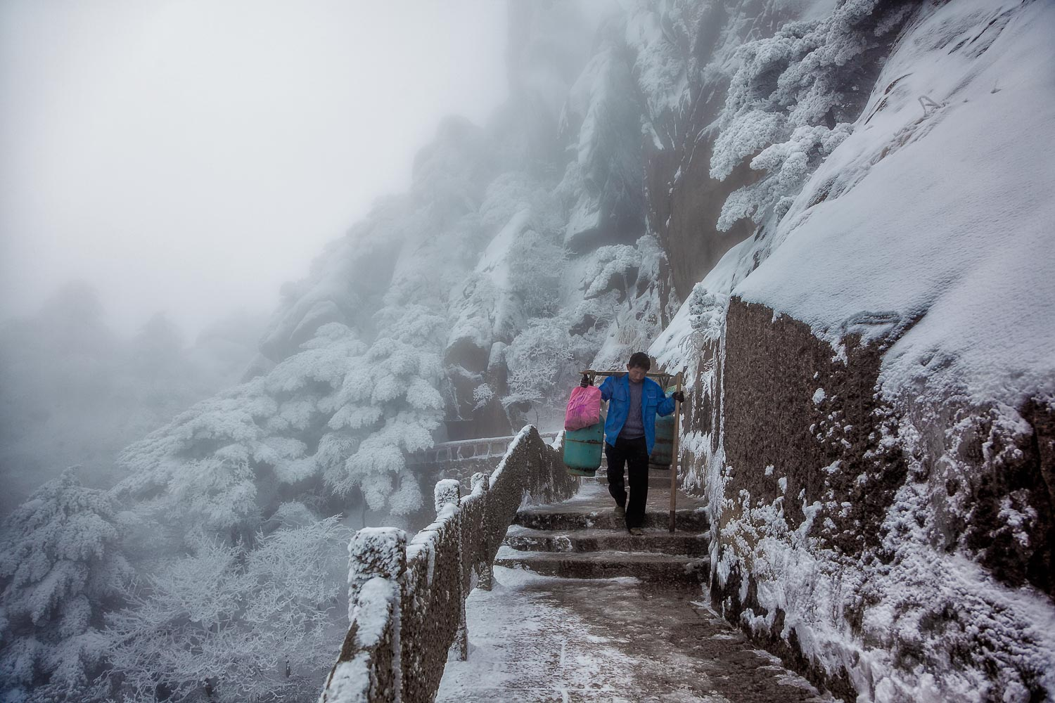A porter, loaded with goods, walks a windy and exposed path on  Huangshan  (i.e., Yellow Mountain),  China .