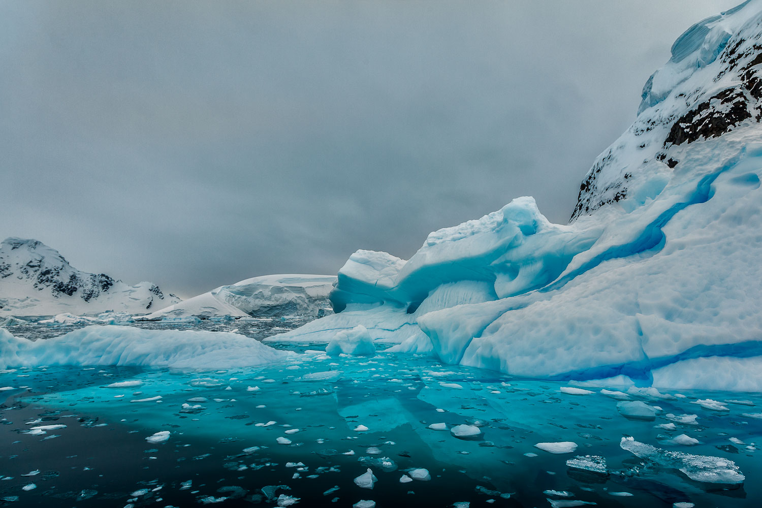 The cool blue of an overcast sky, ice and water make for a particularly melancholy mood of ice and snow on   Paradise Harbour, Antarctica  .