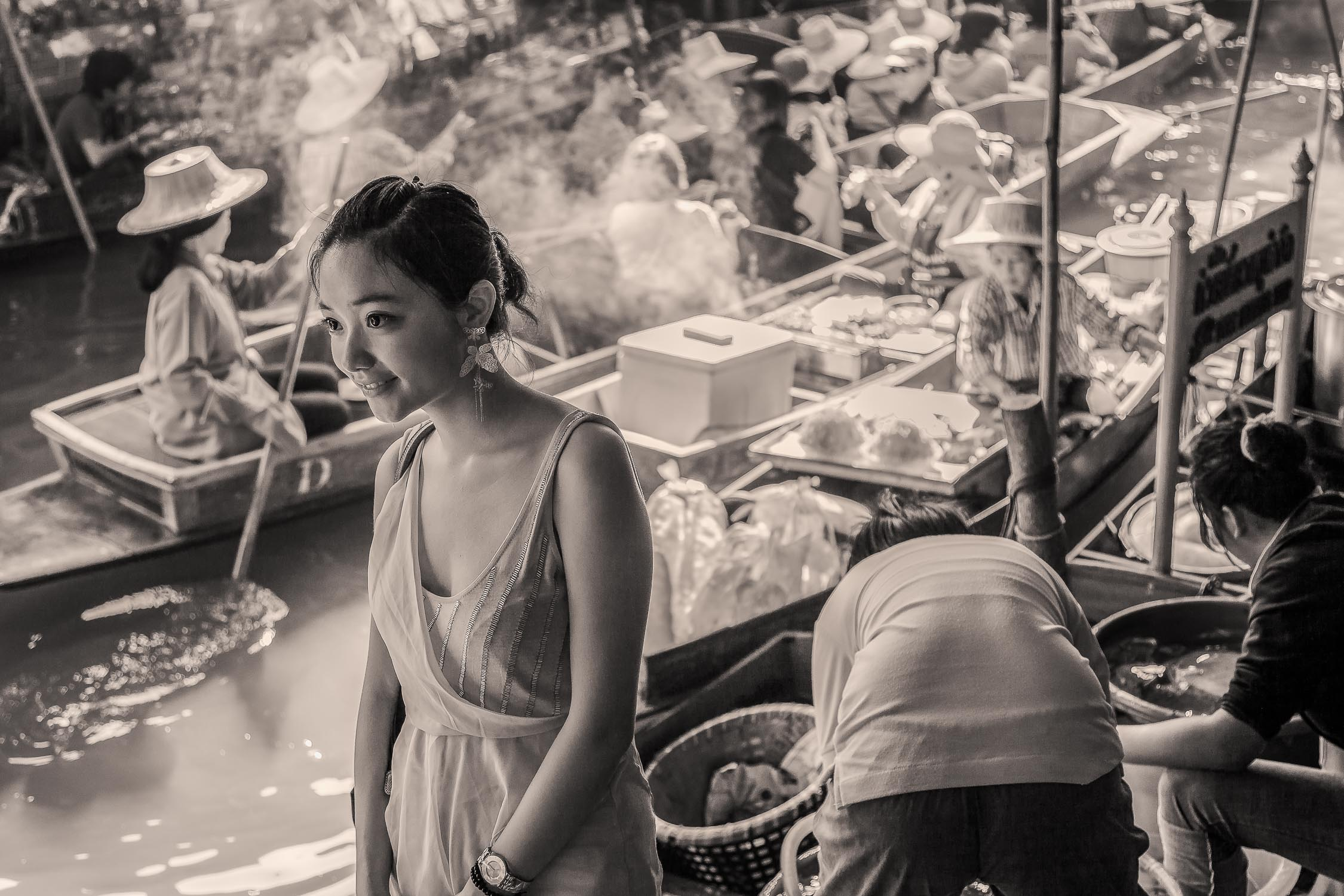 A young woman amidst the hustle and bustle of the  floating market  near  Bangkok  in  Thailand  .
