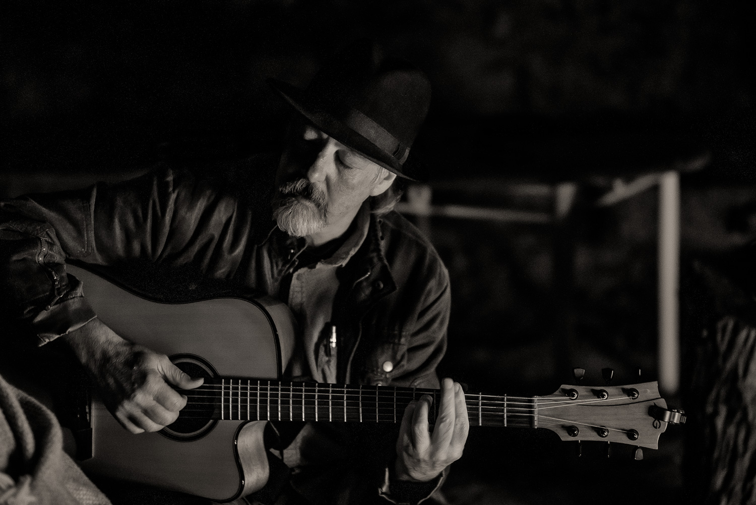 Steve Geohegan , bass player extraordinaire with the  Murder Of Crows , strikes a reflective chord playing an accoustic guitar by campfire light at  Murrayville , Australia.