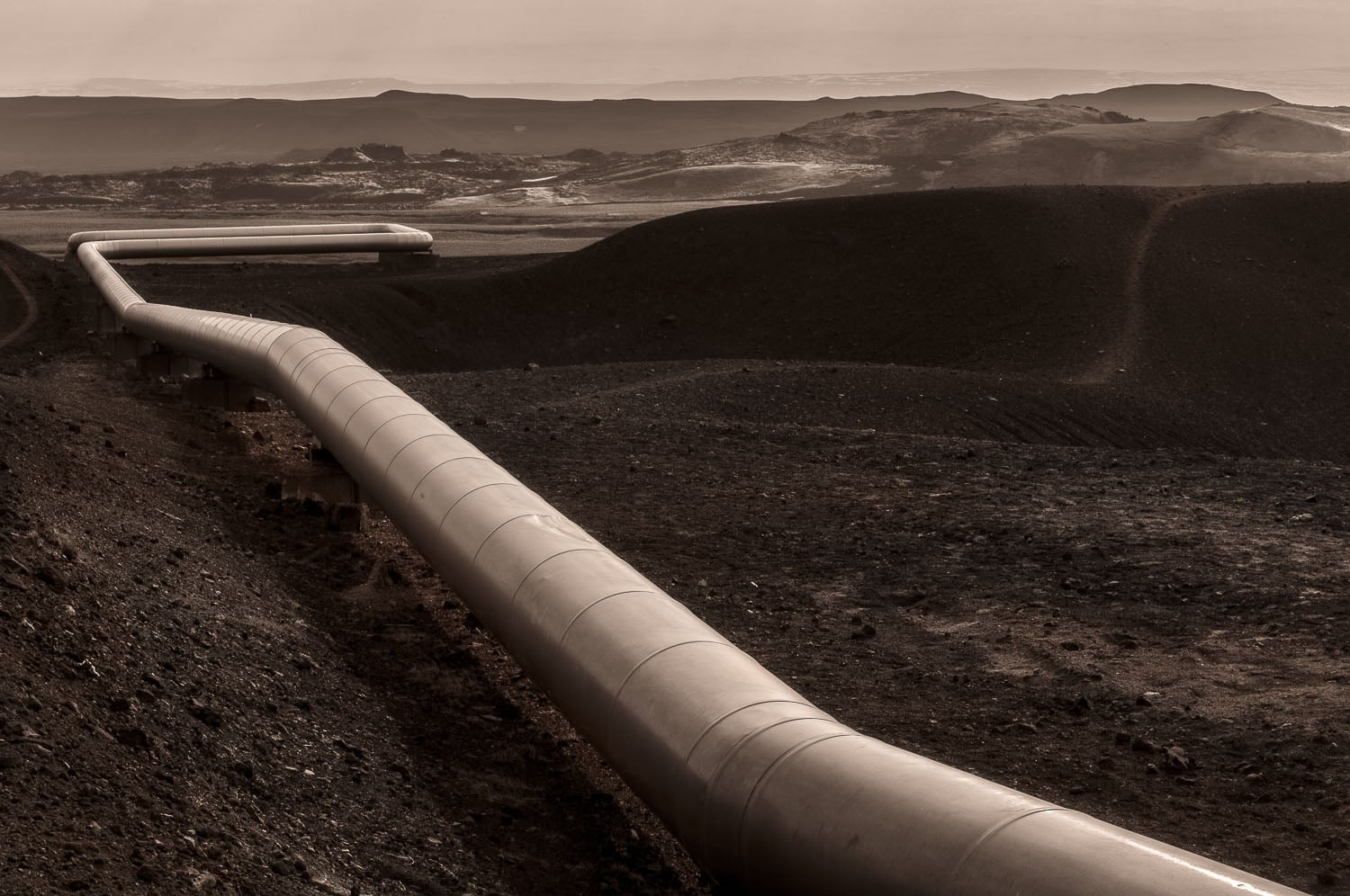 A large pipe transfers steam through the landscape near the    Viki Crater    not far from the town of    Myvatn    in    Northern Iceland   .