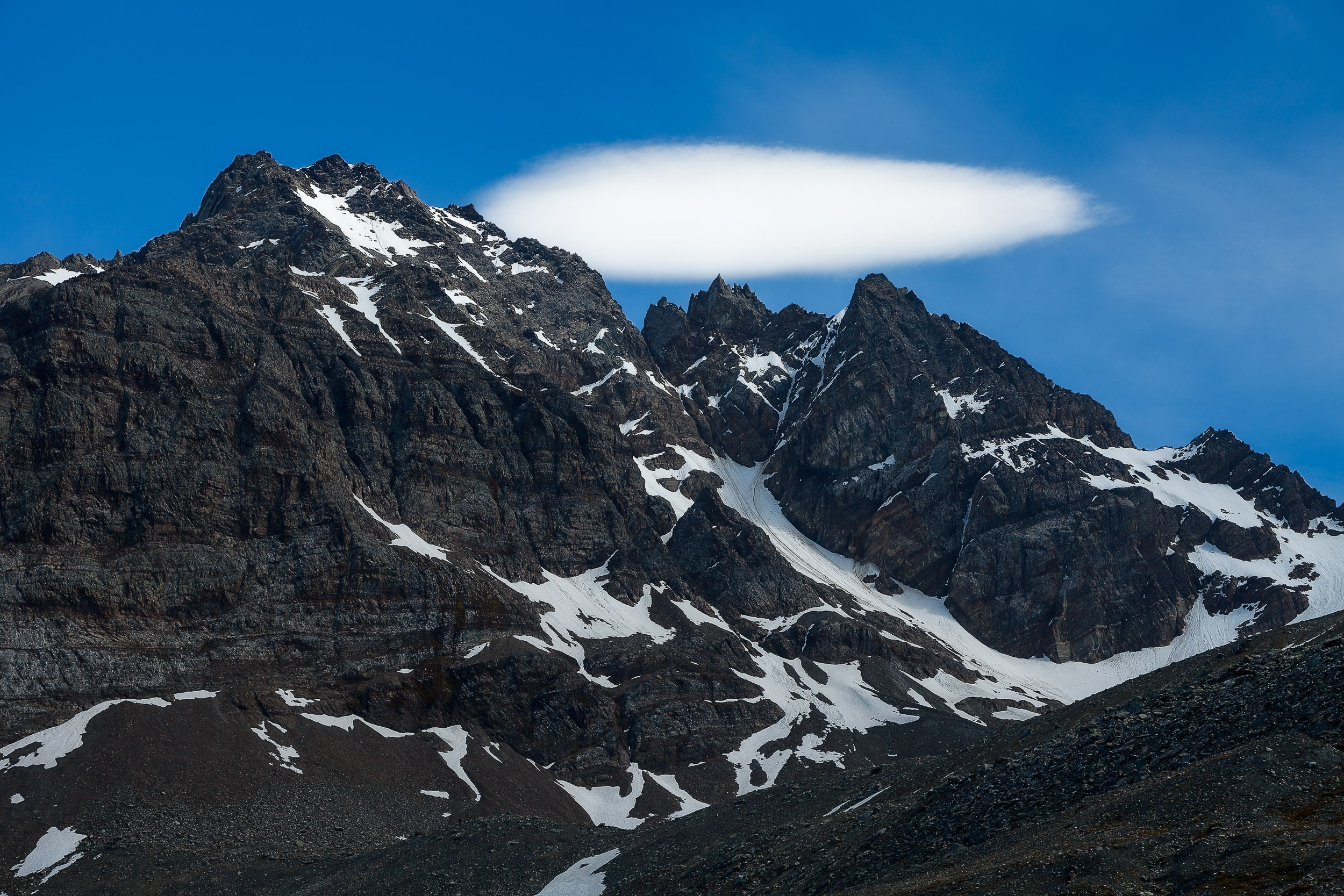A spectacular view of a low lying cloud hovering over mountain peaks on  South Georgia Island .