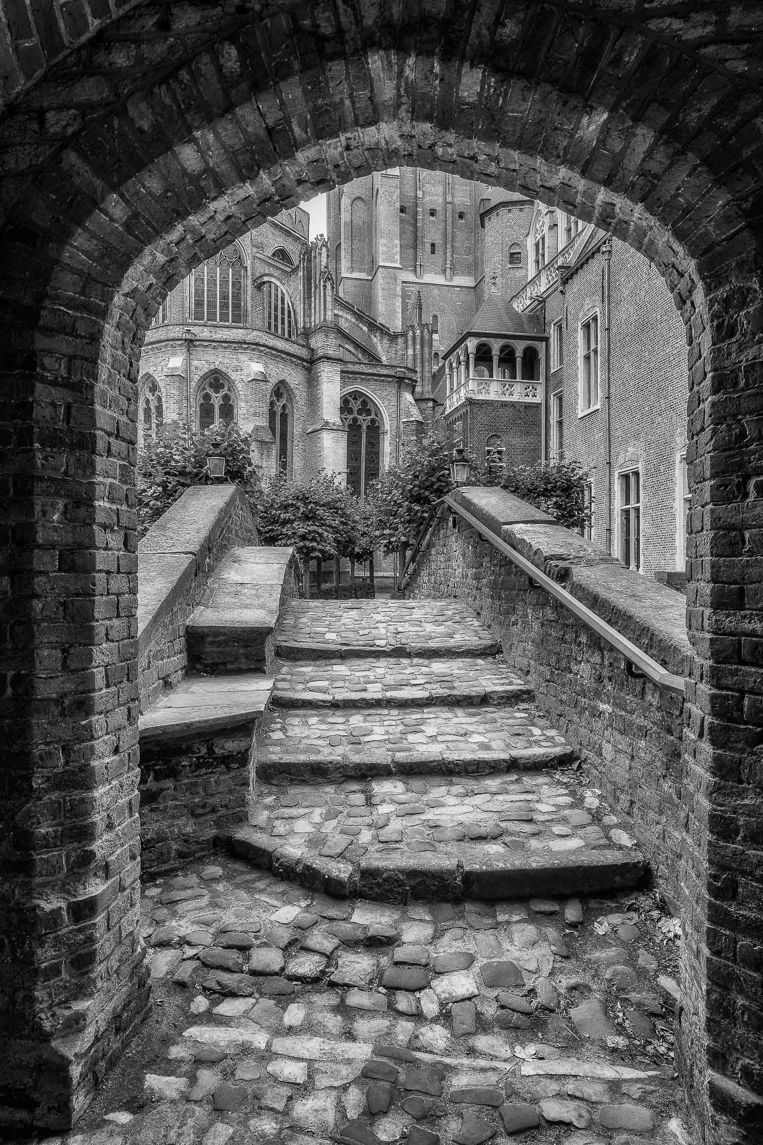 A classic view looking through an archway onto a bridge and onwards towards historic buildings in    Bruges, Belgium   .