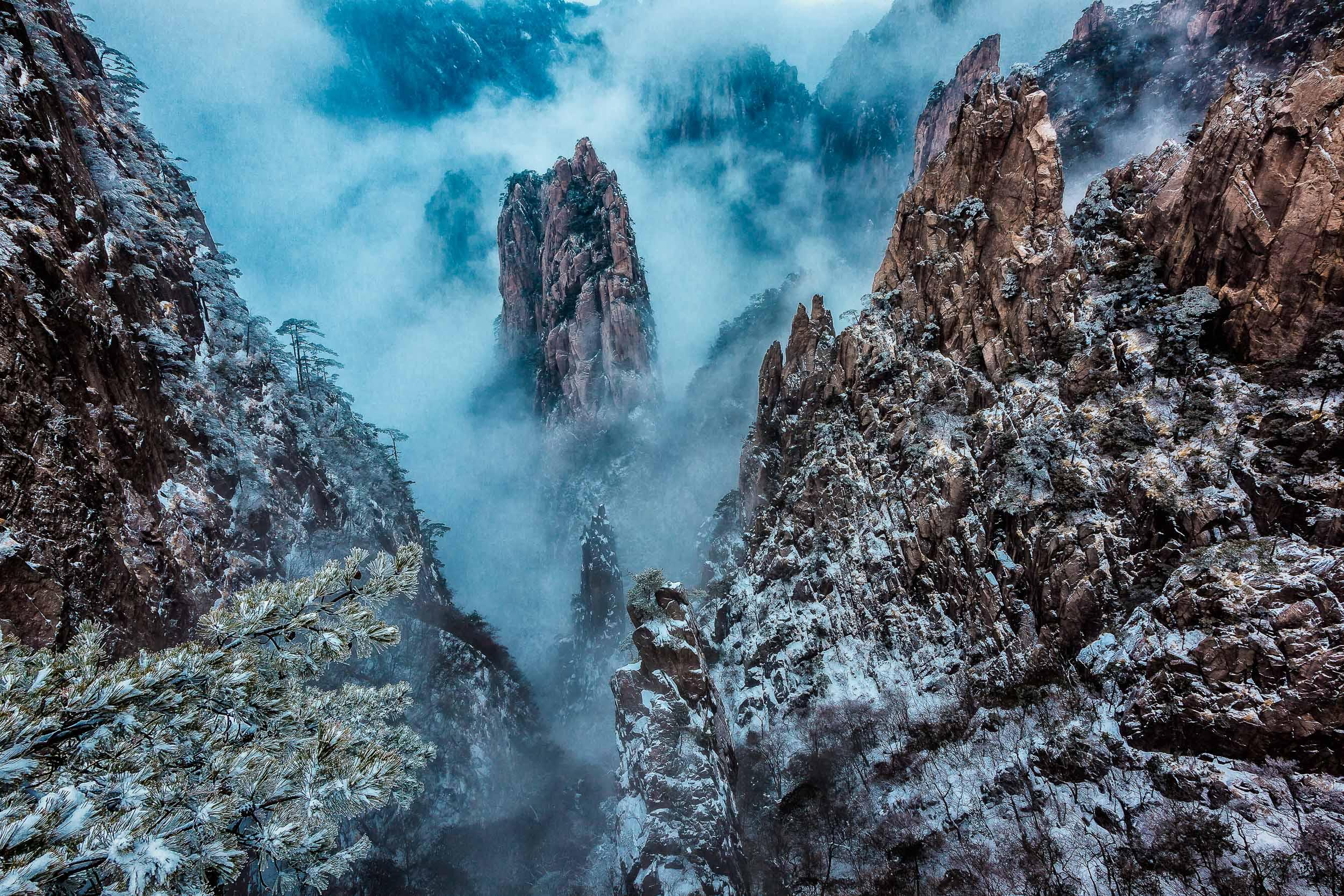 Mist swirling around peaks of stone on    Huangshan    (i.e., Yellow Mountain),    China   .