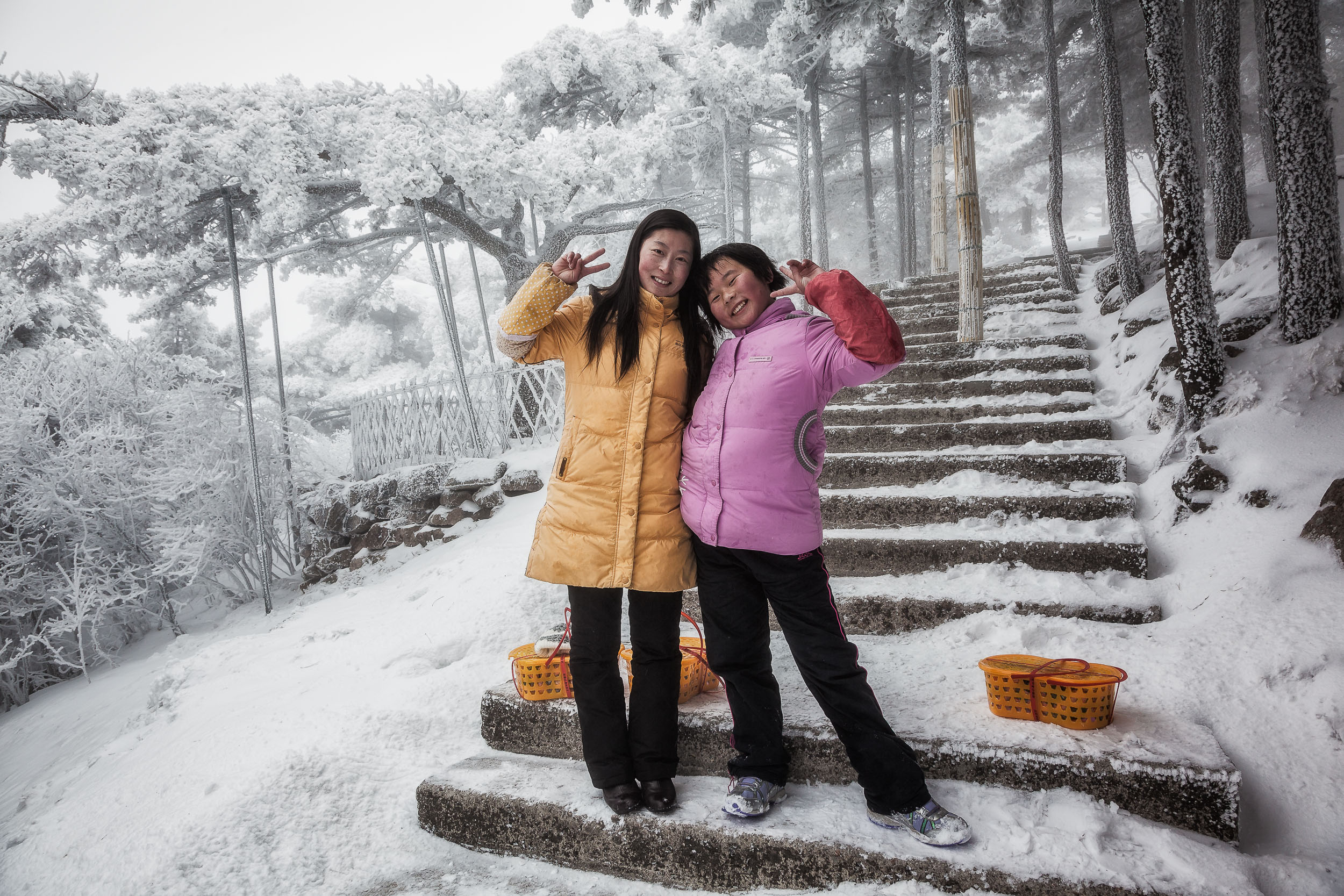 Two girls pose for a photo with the    'V for Victory'    on the slopes of    Huangshan    in eastern    China   .