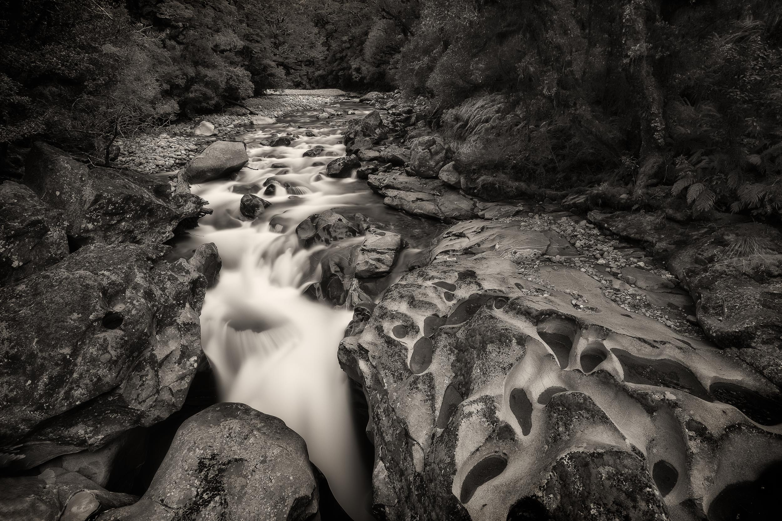 A fast moving    river cascades over rocks    near    Milford Sound, New Zealand   .