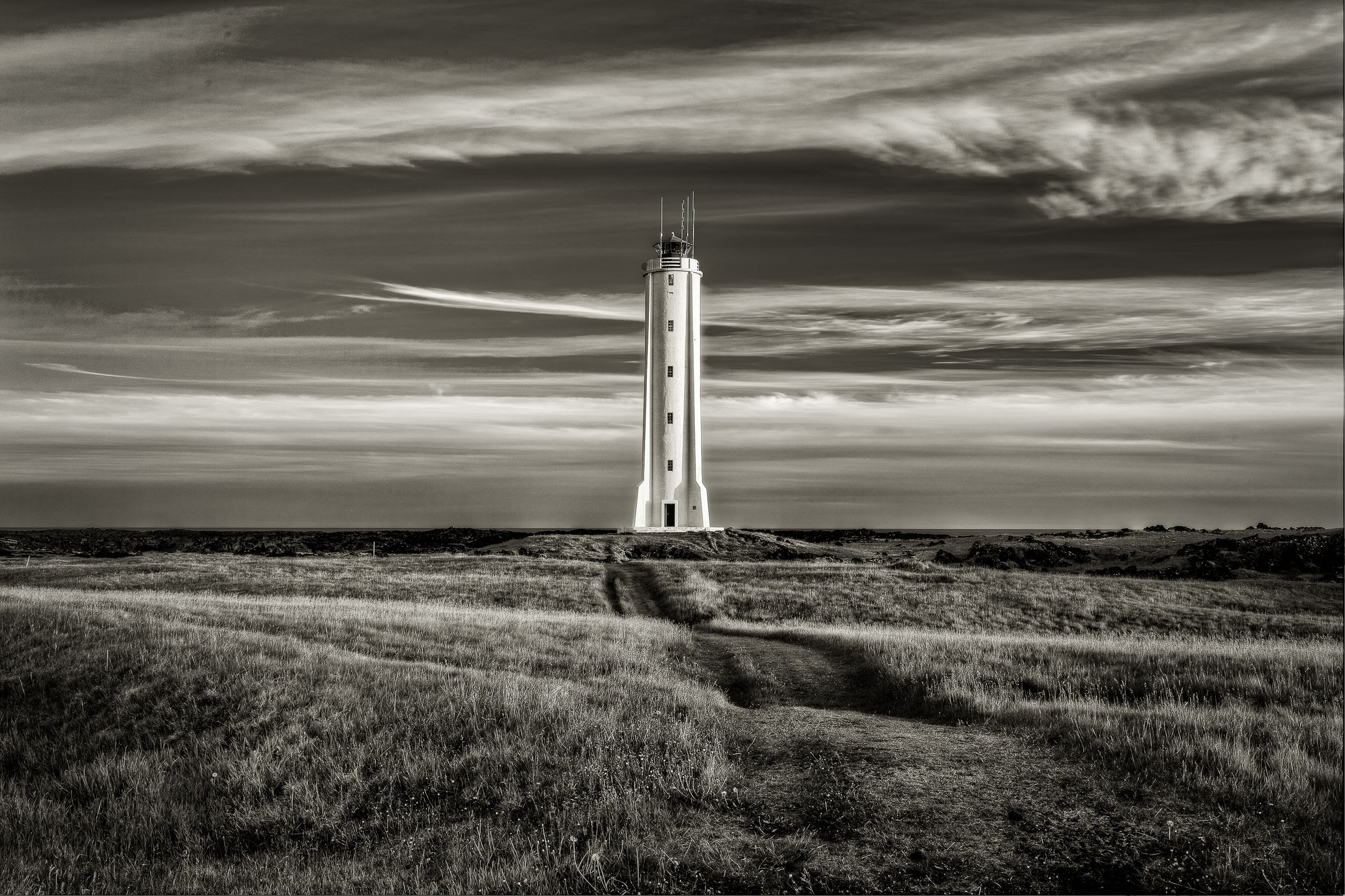 A    lighthouse    stands, strong and alert, at the edge of a field in rural    Iceland   .