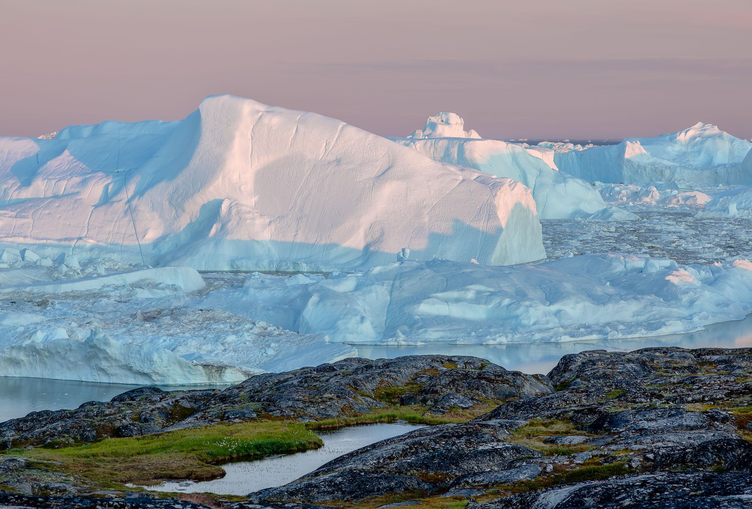 Delicate light illuminates a    gigantic iceberg    on the edge of the    Ilulissat Icefjord    in    Greenland   .