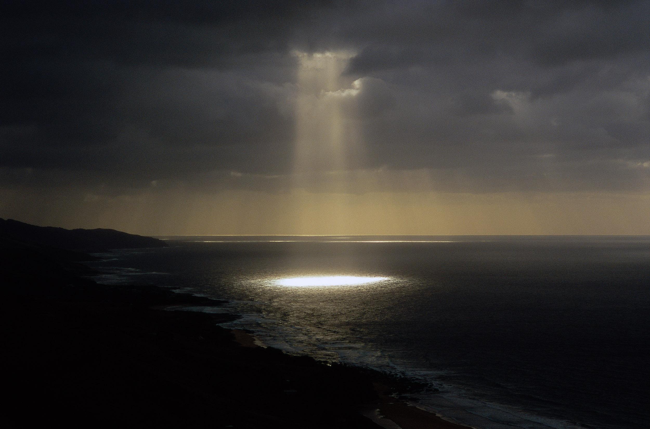 God rays  illuminate the sea under a dark, stormy sky near  Apollo Bay , along Australia's Great Ocean Road.