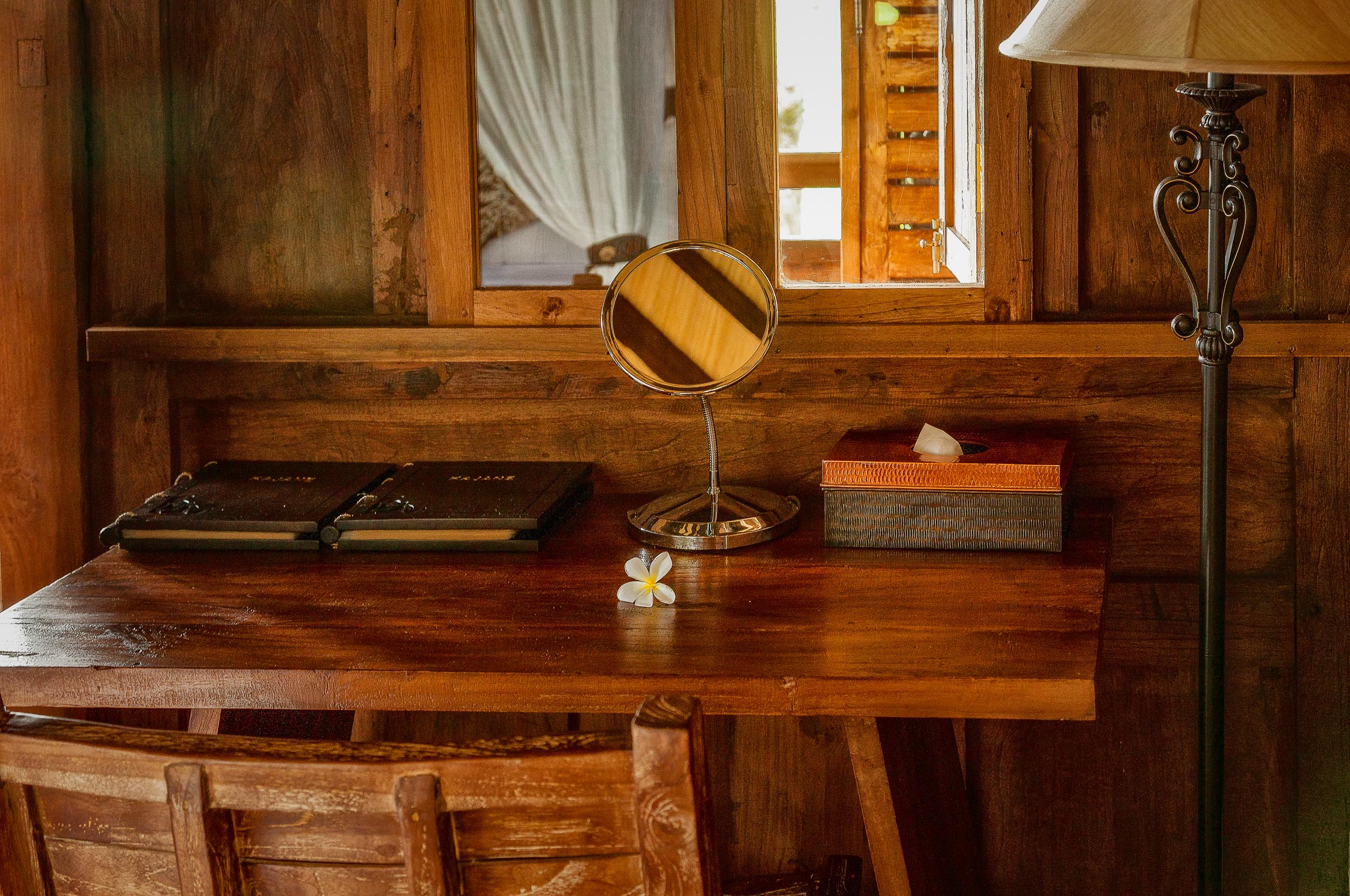A  mirror reflecting light and shadow  atop a lovely, simple wooden desk at  Kajane Mua, Bali .