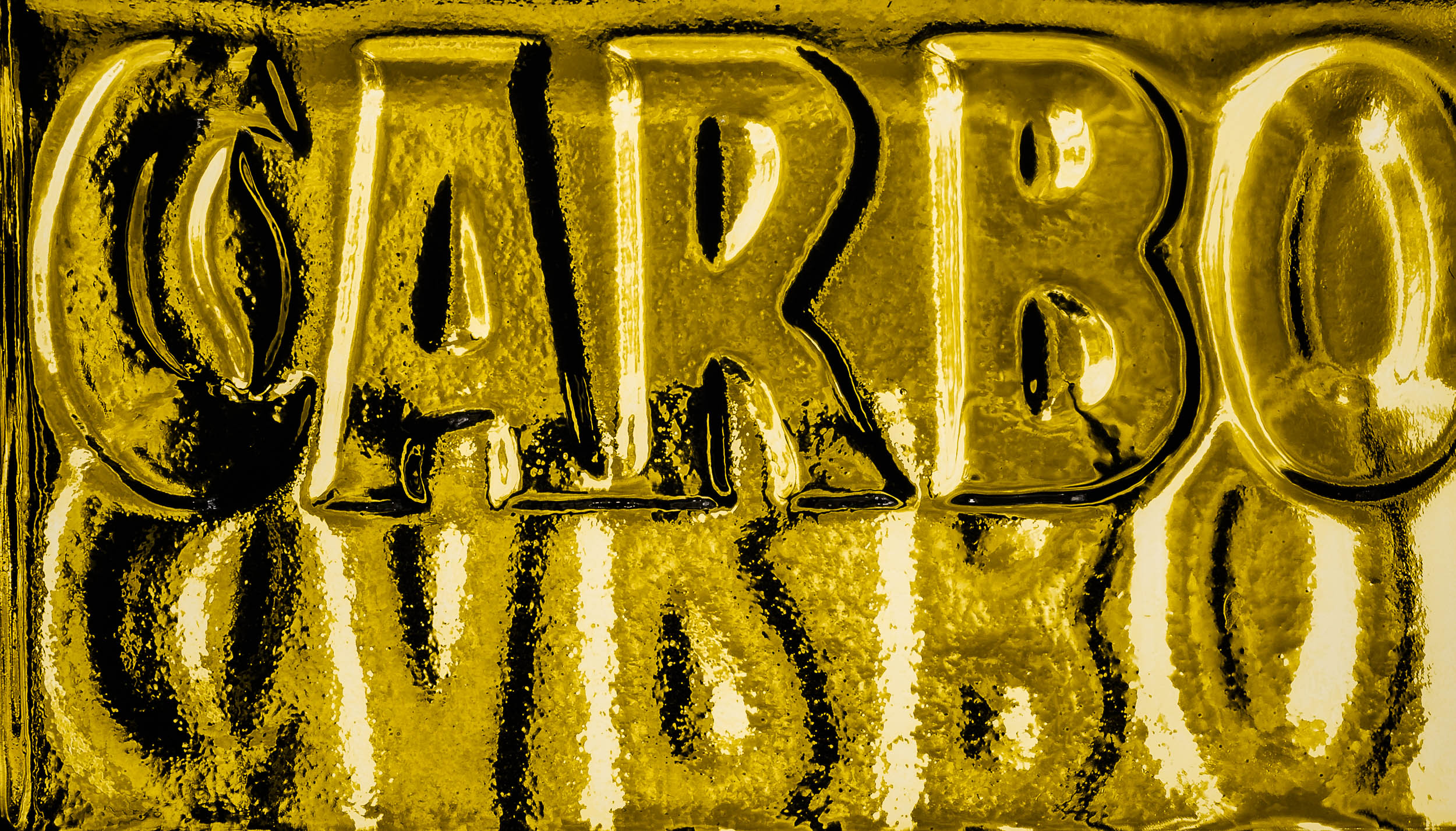 Bold letters, bathed in gold . A close up image where  abstraction  has been used to produce a  visually dynamic result .