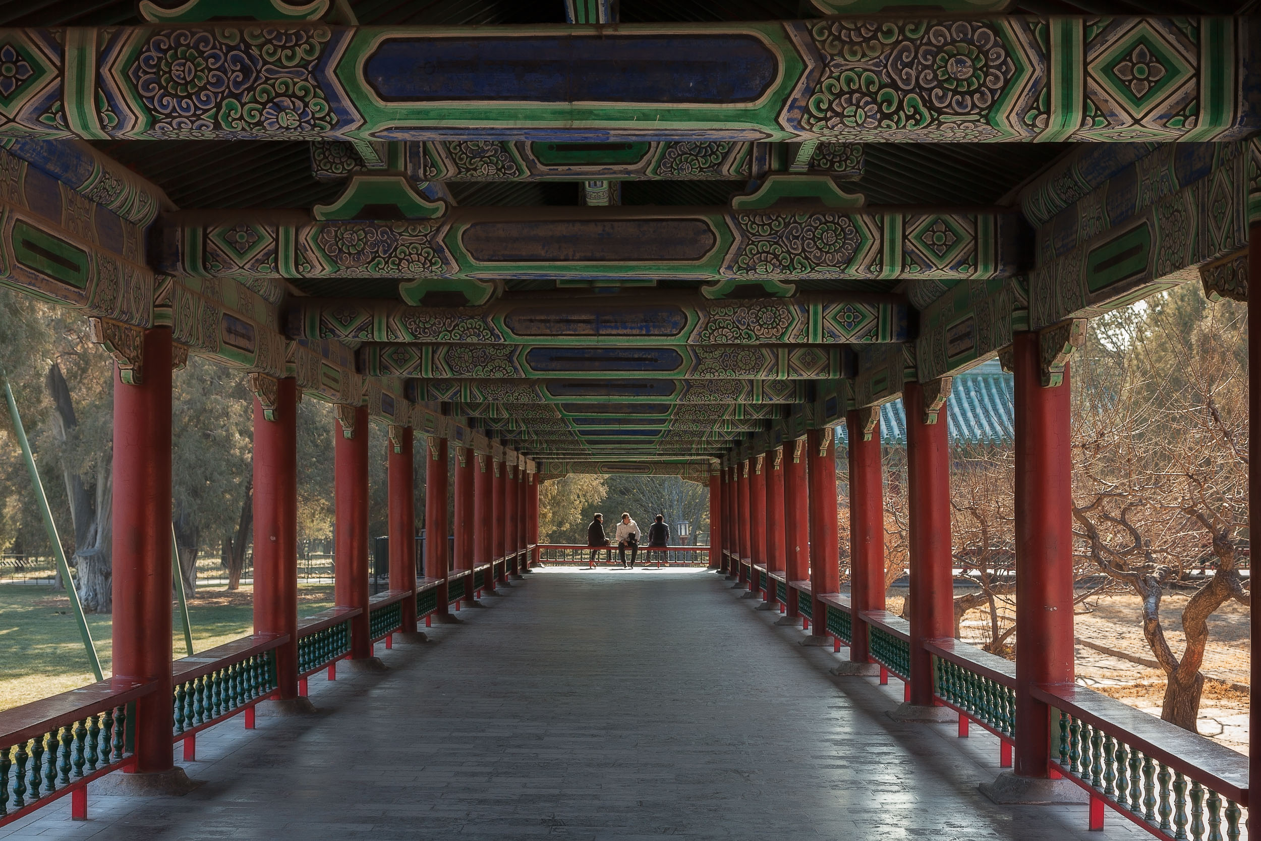 A peaceful view of  three men relaxing in the sunshine  at the end of a long verandah at the  Temple of Heaven  in  Beijing, China .