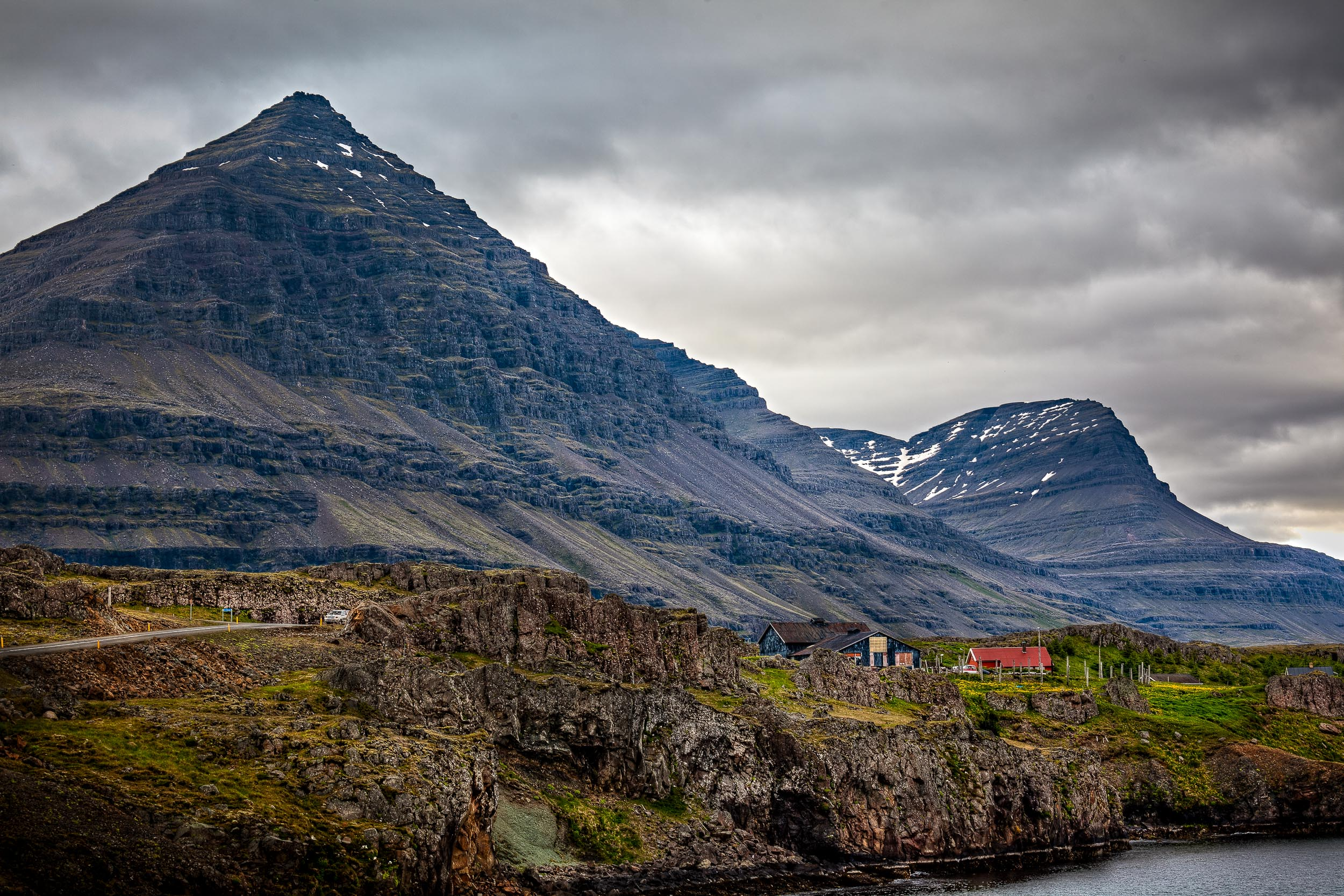 A    tiny hamlet   , set against    stunning mountain scenery   , by the coast in    Northern Iceland   .