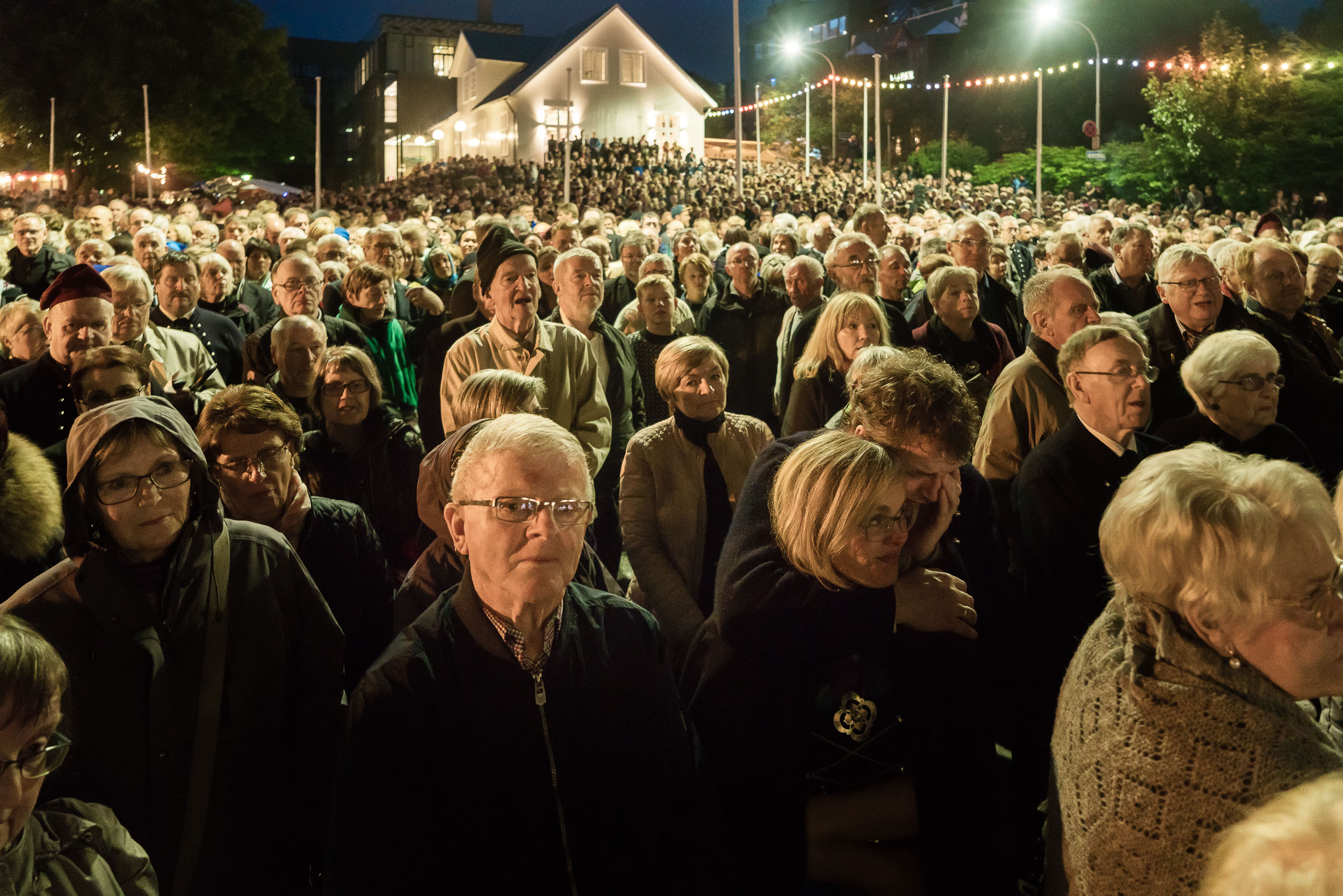 A    large crowd    listens to sombre music from the local    Salvation Army Band    during the    St. Olaf's Day Celebrations    on a summers evening in    Tórshavn, Faroe Islands   .