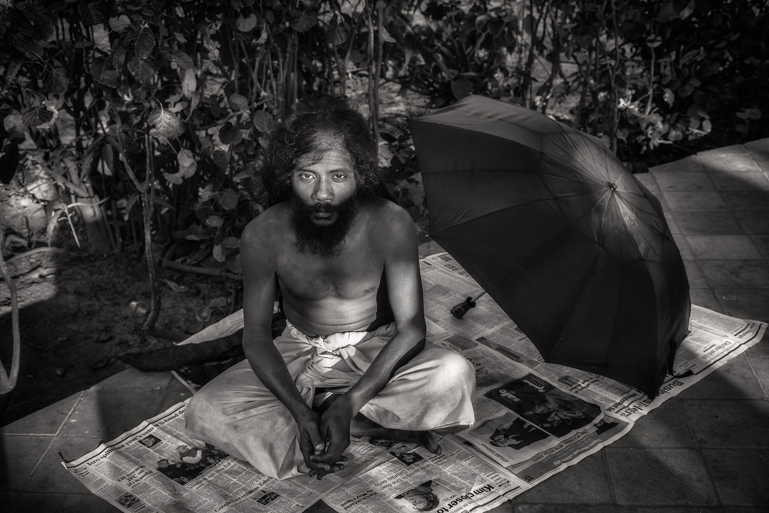 Black and white portrait    of a yogi in India    resting in the grounds of a temple complex by the banks of the    Hooghly River    in    Kolkata.