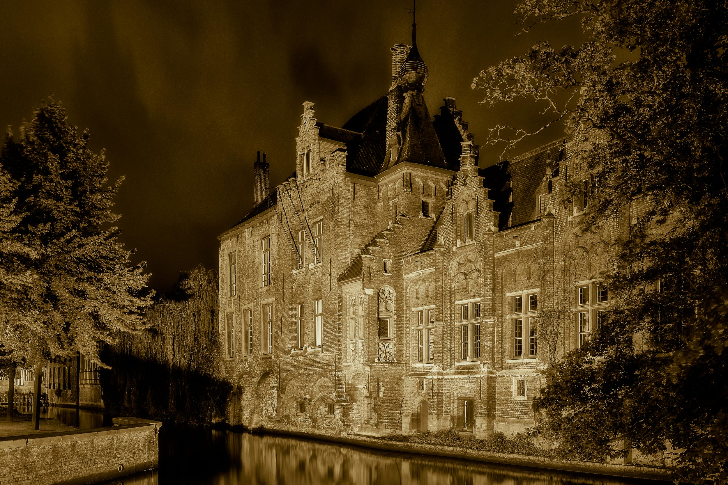 Artificial lights illuminate an    historic building    on the canal in    Bruges, Belgium   .
