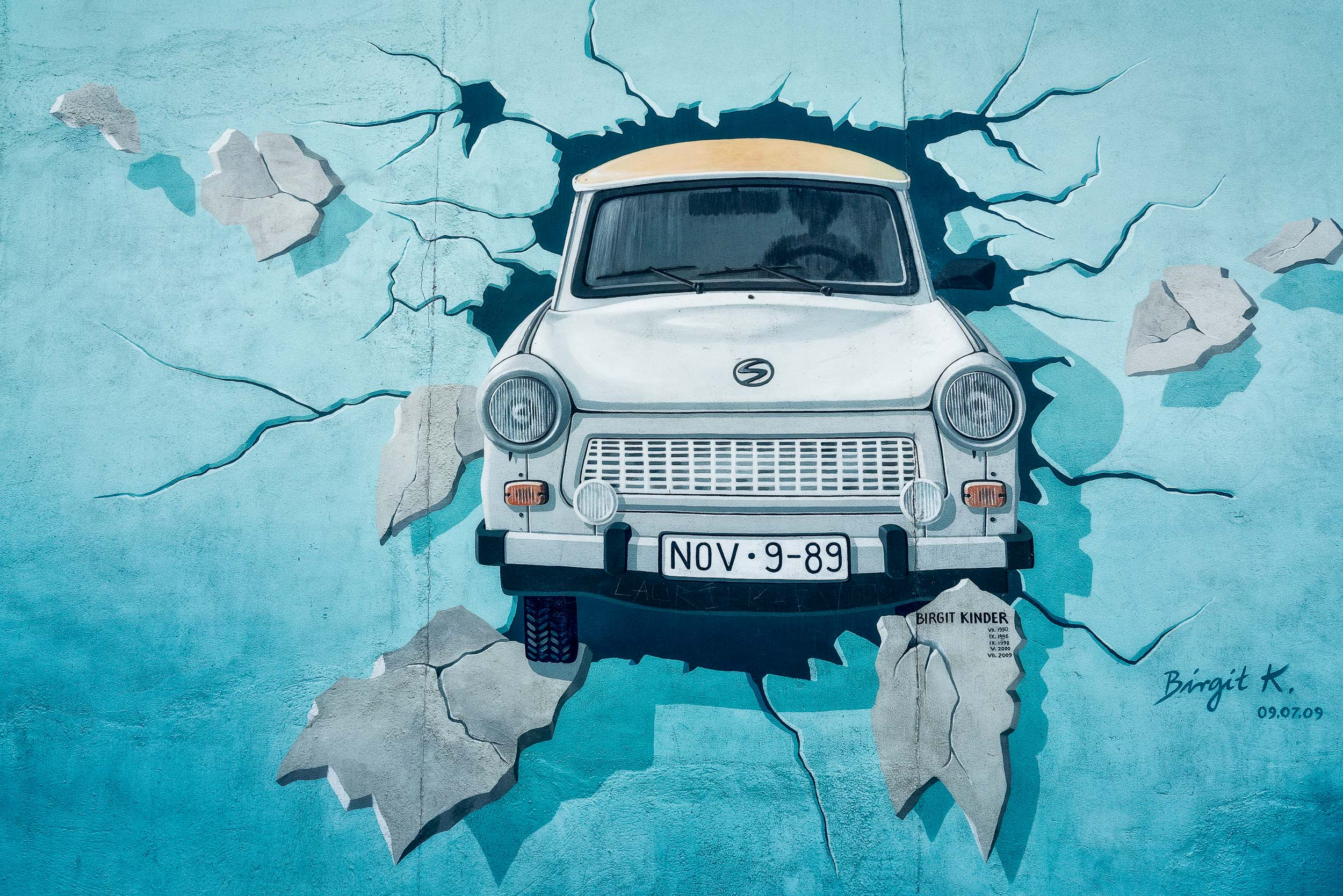 The artist  Birgit Kinder's painting  of a soviet manufactured  Trabant car  breaking through the  Berlin Wall  shows a license plate displaying the date the wall fell.