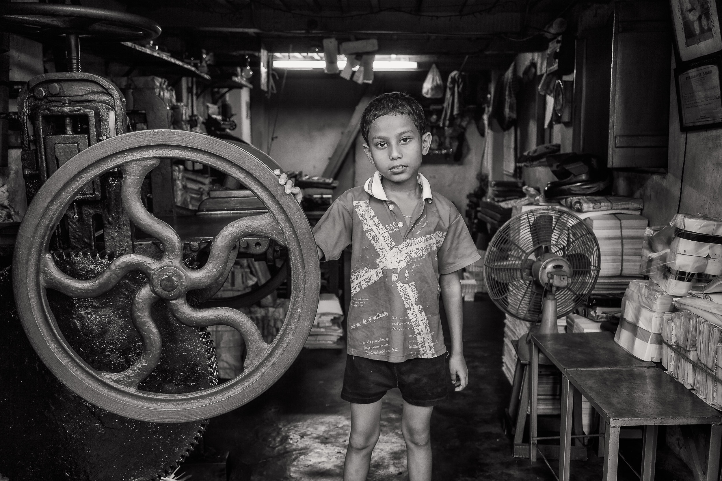 A lovely  formal portrait , in black and white, of a  young boy  in his father's print workshop in  Kolkata, India
