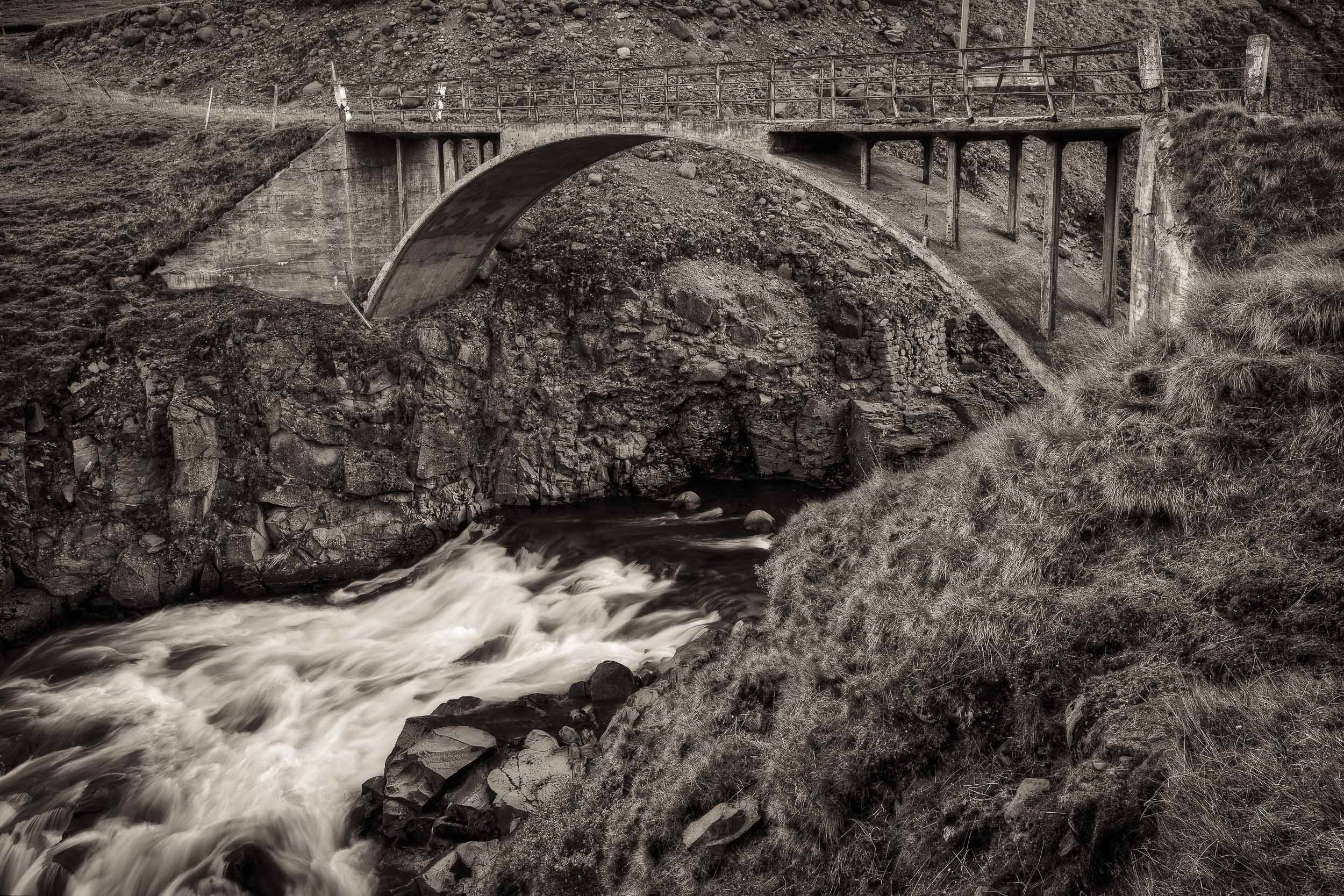 An  old stone bridge  spanning a  fast moving stream  in rural  Iceland .