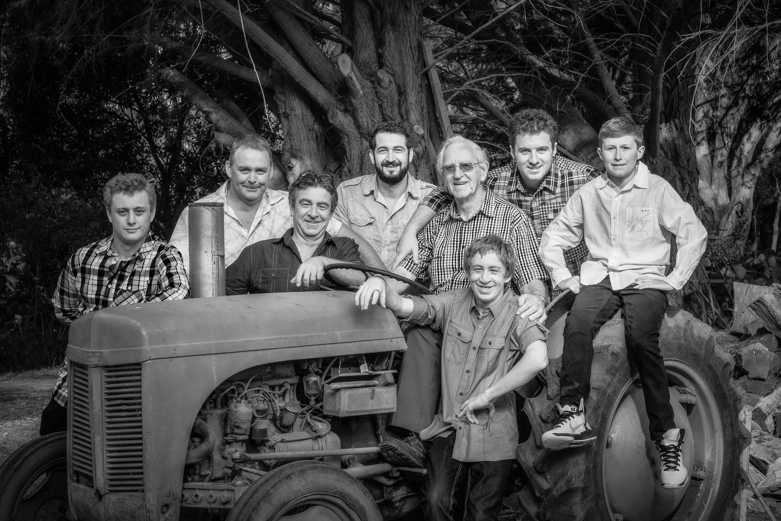A  group photograph  featuring  three generations of men  on a  tractor  in  Hamilton, Australia .