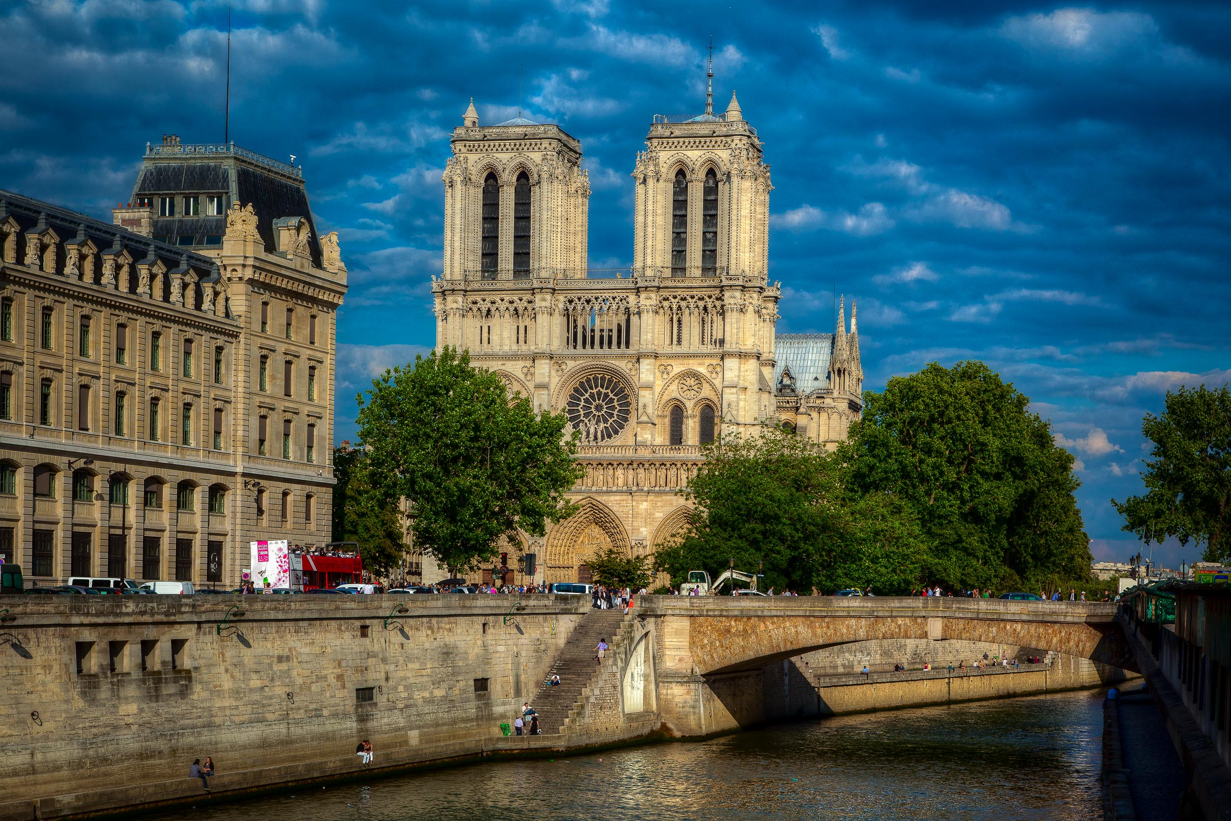 A sunny day view of    Notre Dame Cathedral    and the    River Seine    in    Paris, France   .