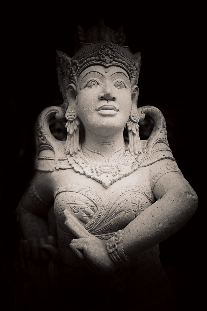 A  stone statue  seen  emerging from the darkness  in a  Hindu temple in Bali, Indonesia .