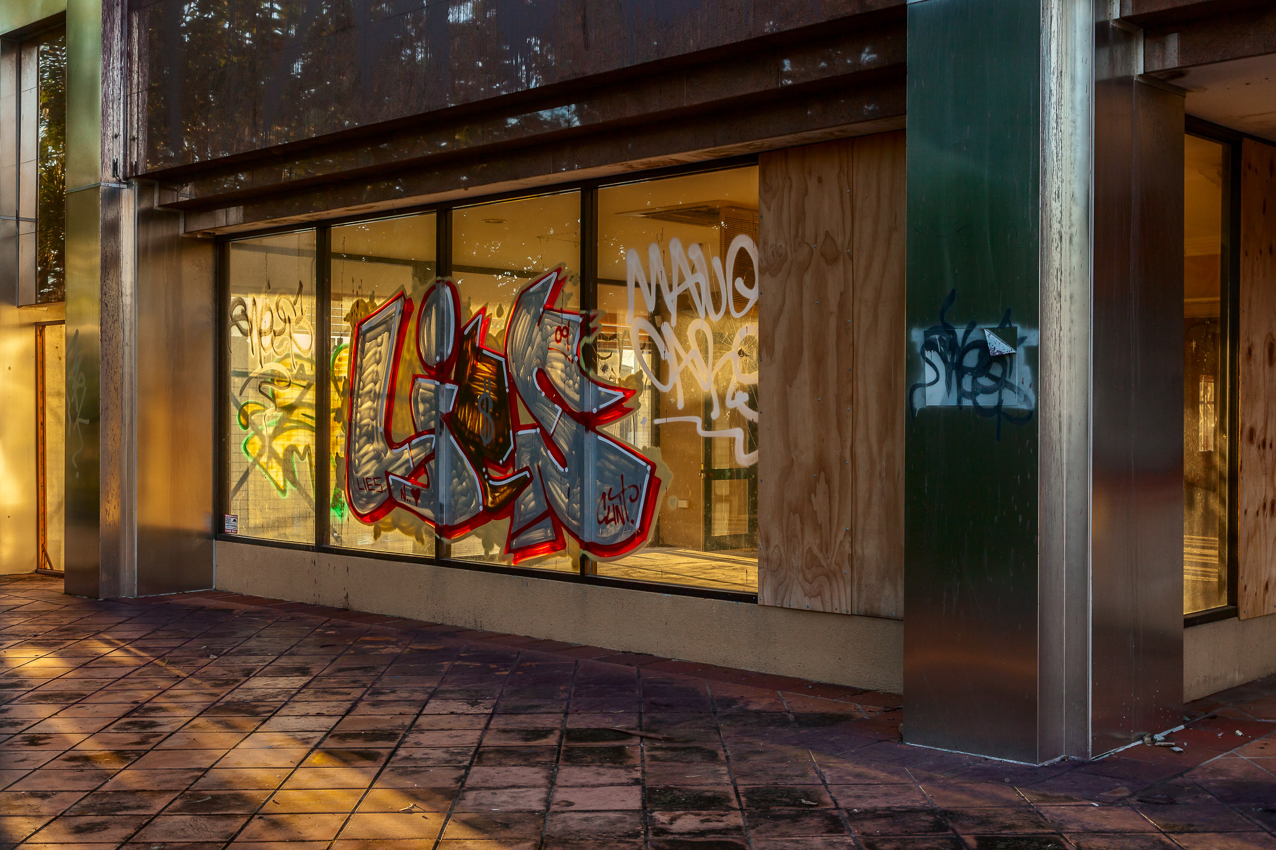 A  vacant store  with a store front that's been  tagged by vandals  at sunset on the  Gold Coast, Australia .