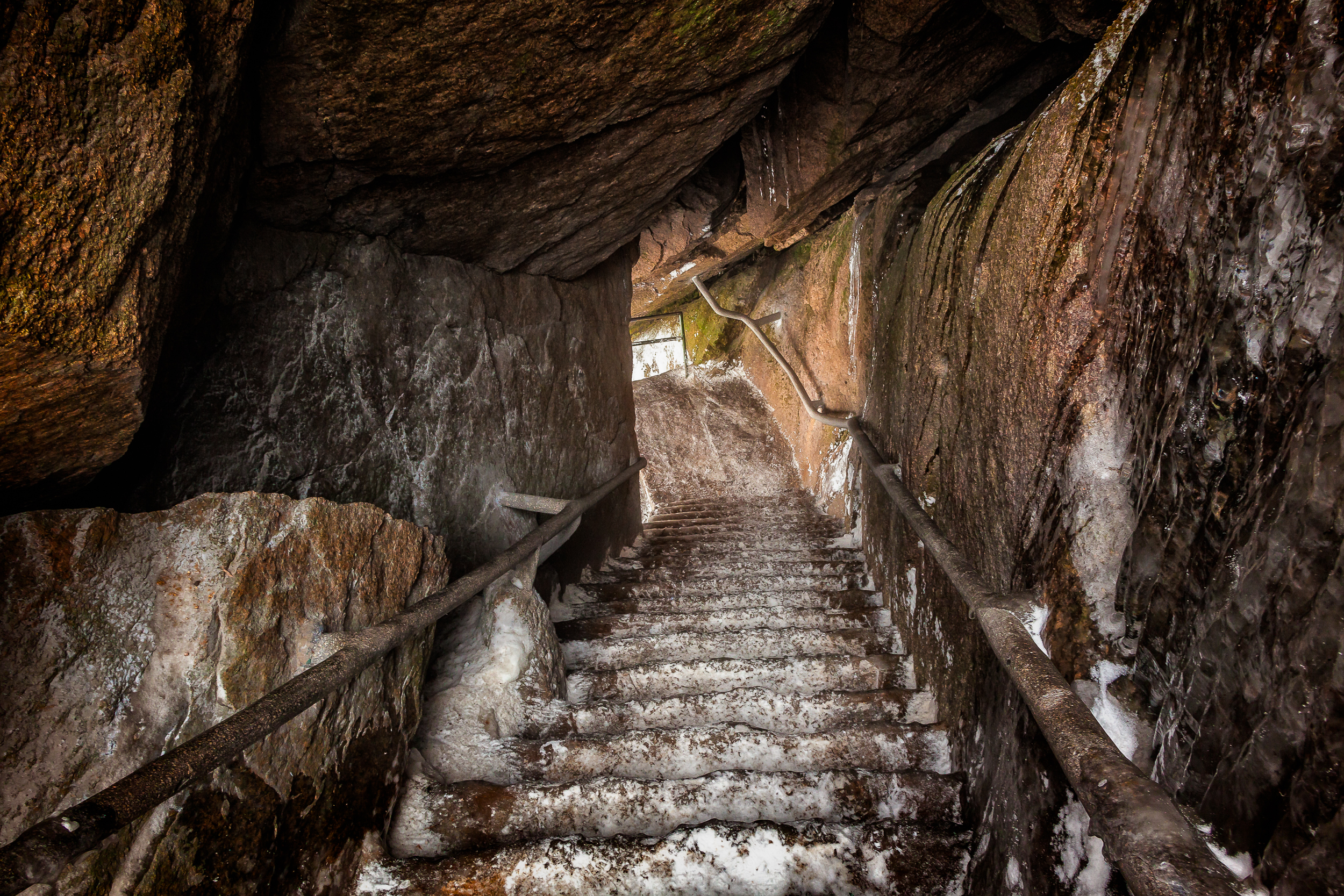 An  icy staircase  takes the hiker  through the rock  and onto the path proper along the spectacular trail on  Huangshan  (i.e., Yellow Mountain).
