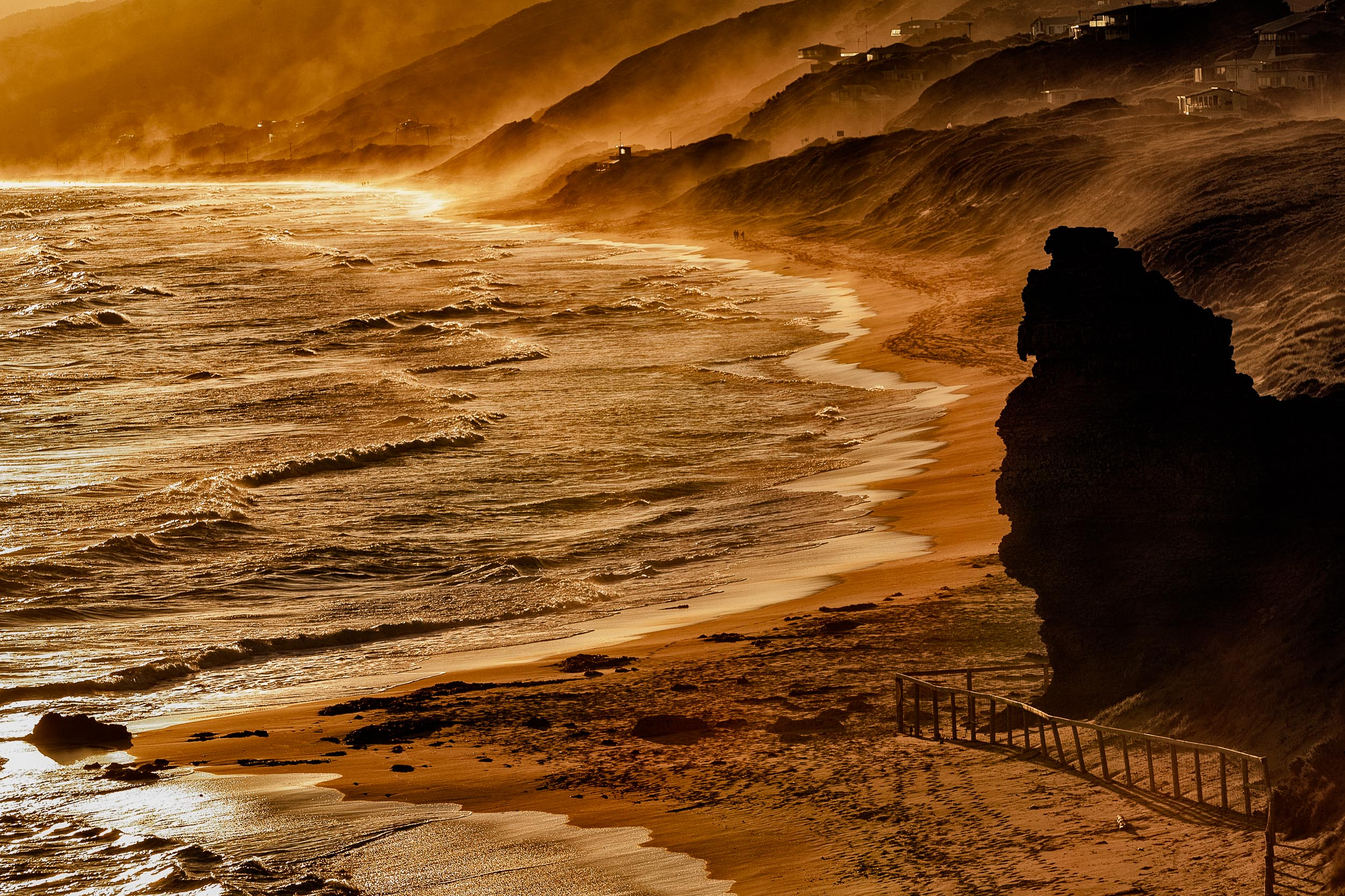 Surf and mist    meet along the    beach at sunset    at    Aireys Inlet    along the    Great Ocean Road    in Australia.