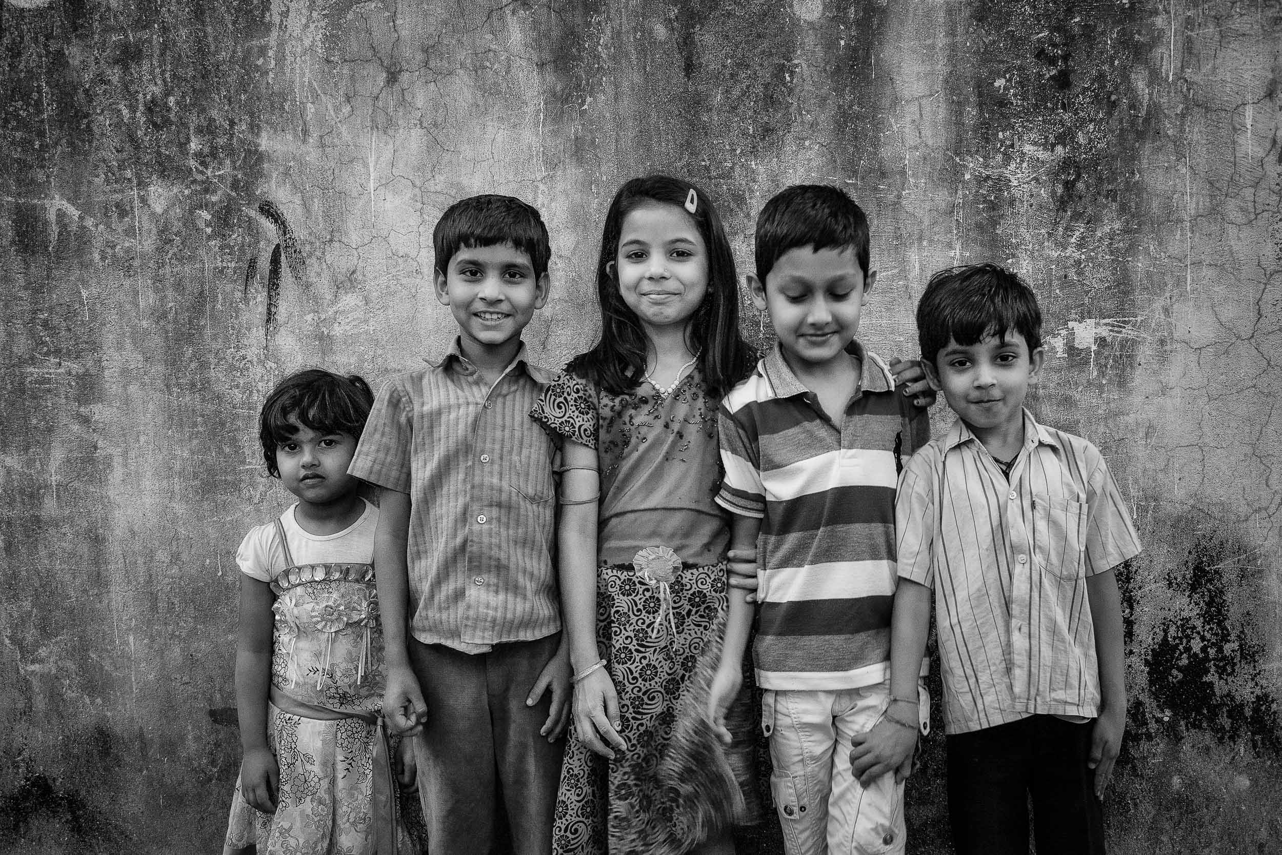 A    group of kids    pose for a photo in an    alleyway    in    Kolkata, India   .