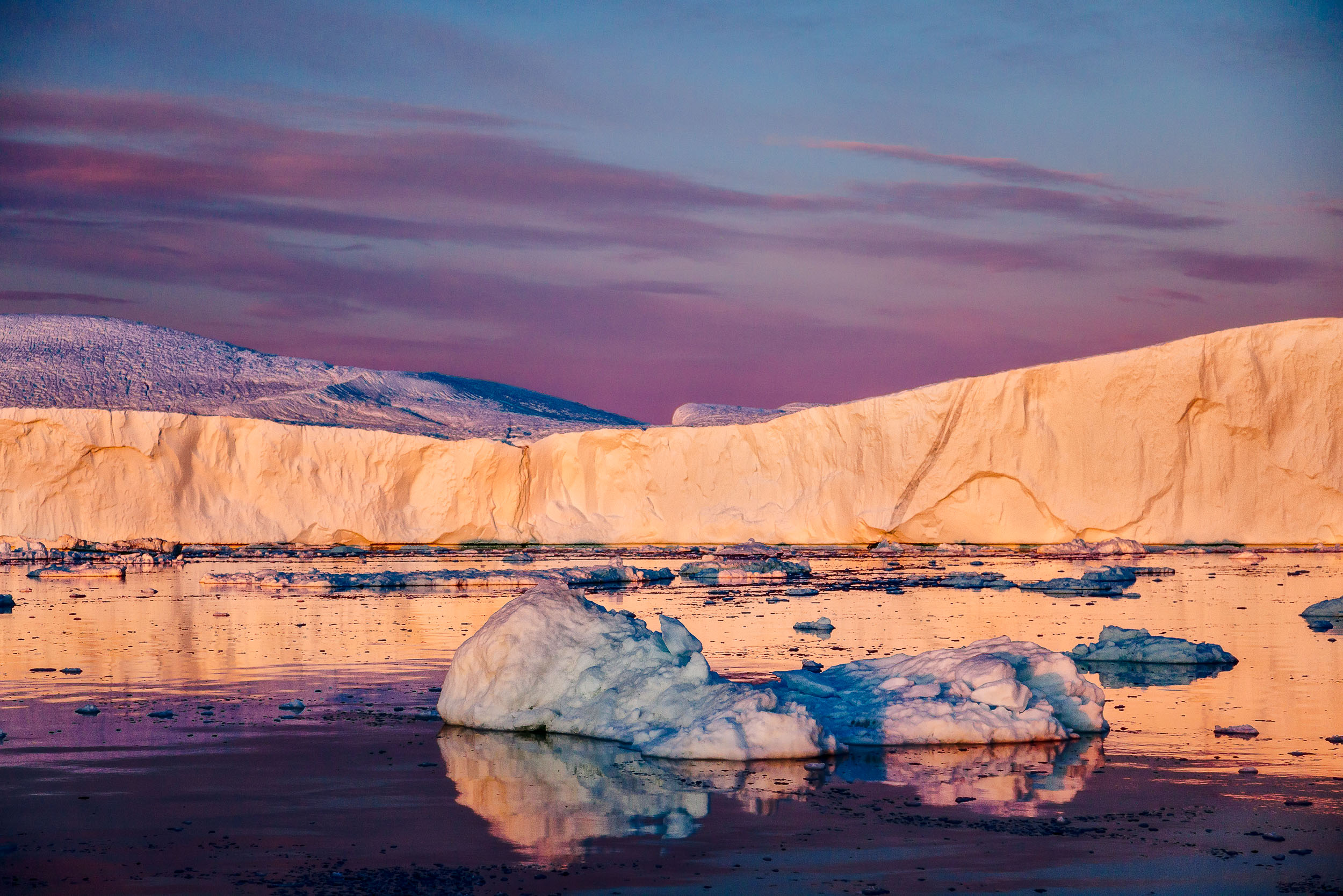 Striking colors and bold light  on display during a  midnight cruise  on the  Ilulissat Icefjord  in  Greenland .