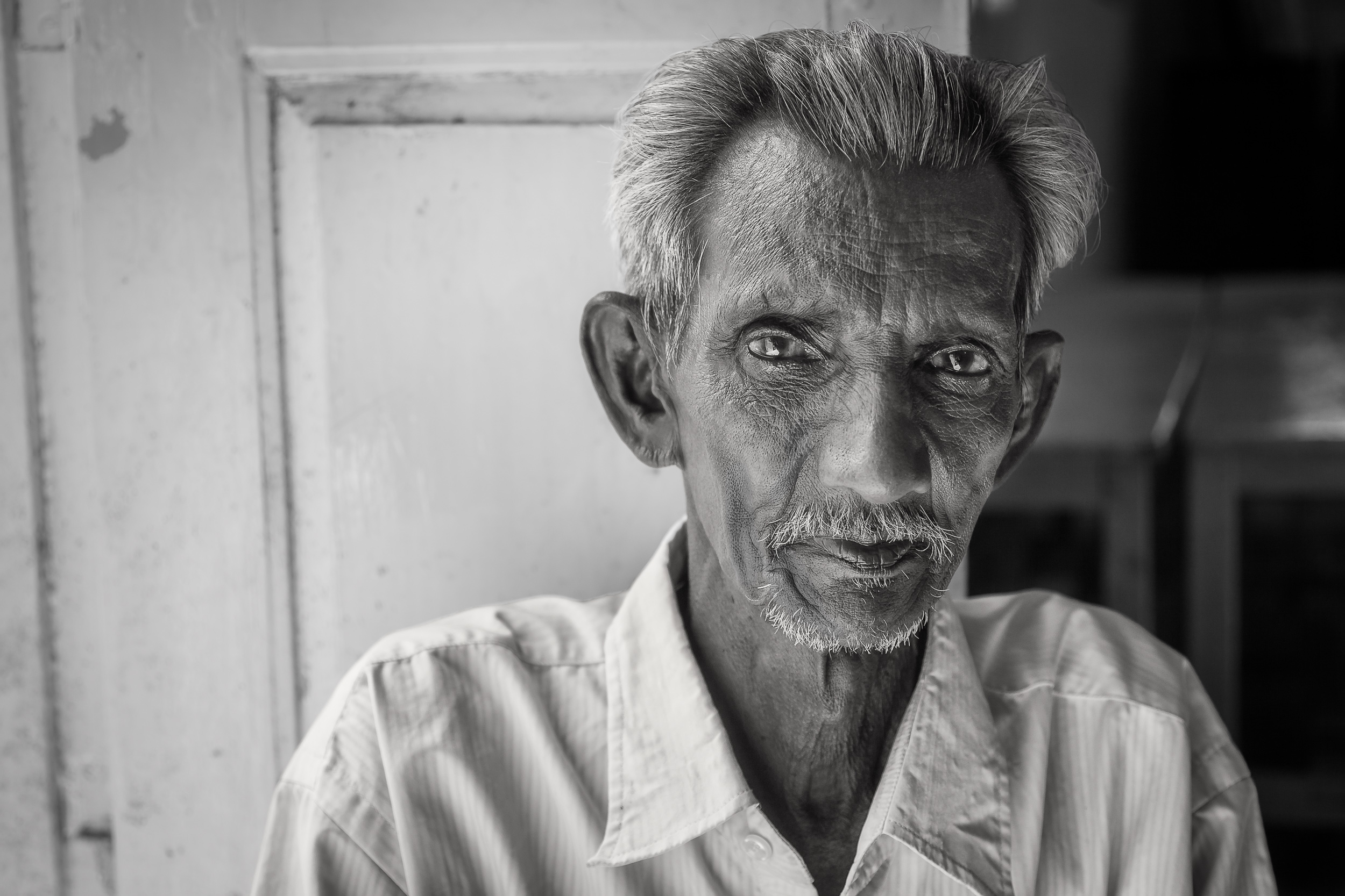 A beautiful    black and white portrait    of an    elderly man    sitting by an open doorway on the outskirts of    Chennai, Indiag