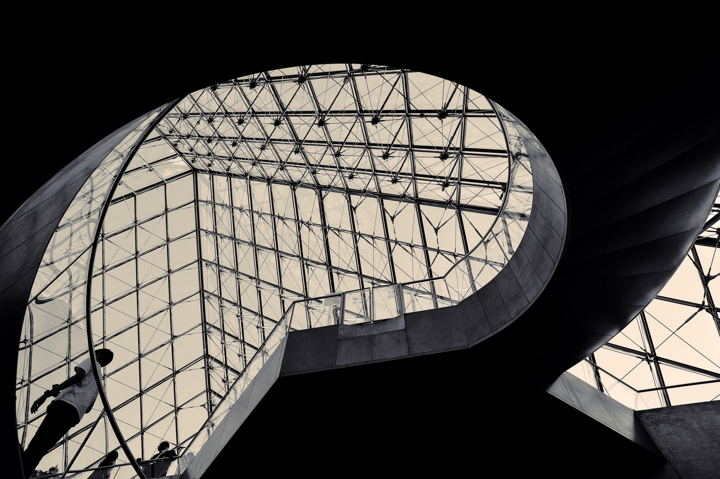 An upward view of a stunning  architectural detail  of a  sweeping staircase and glass roof , in the  Louvre  in  Paris, France .