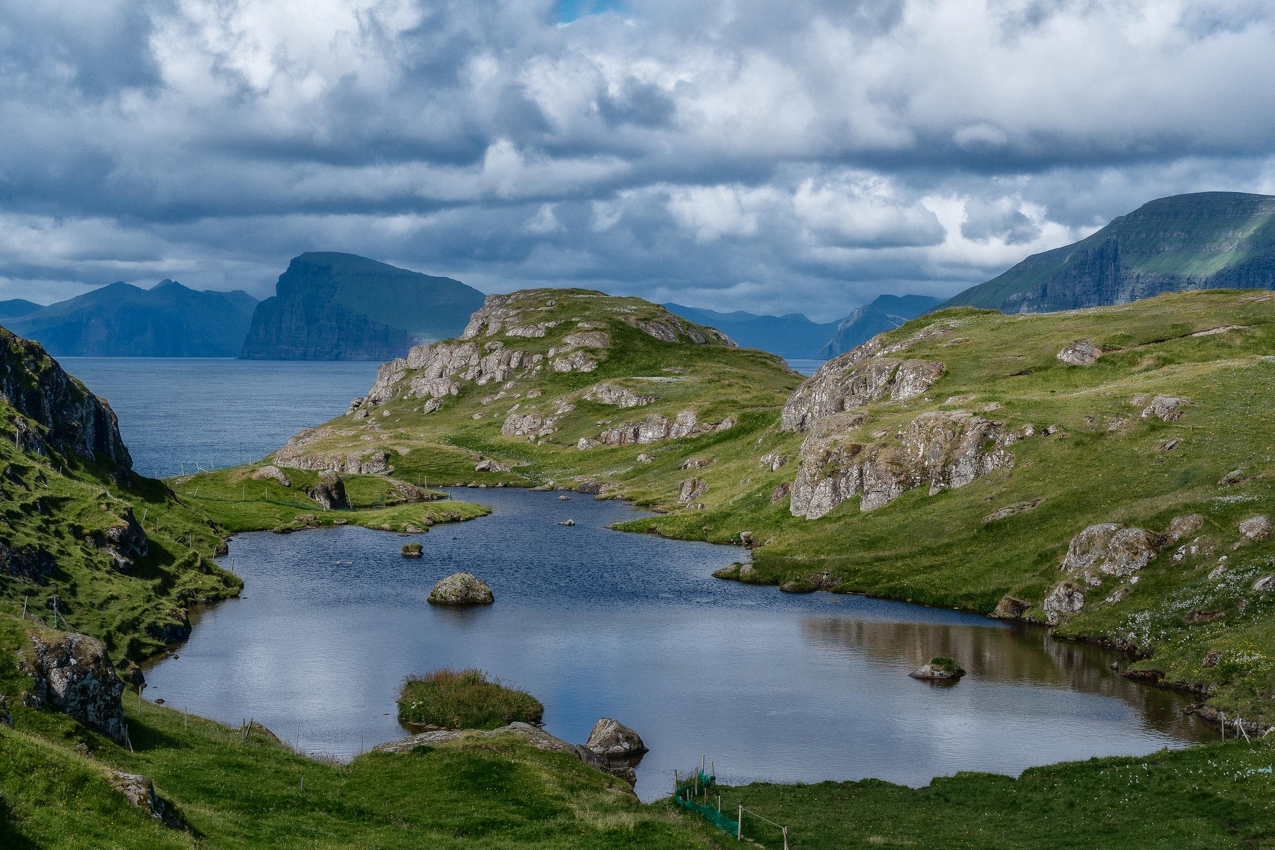 Green rocky terrain and blue waters, underneath a stormy sky, provide  an incredibly beautiful outlook  near the town of  Skopun  on the  island of Sandoy  in the  Faroe Islands .