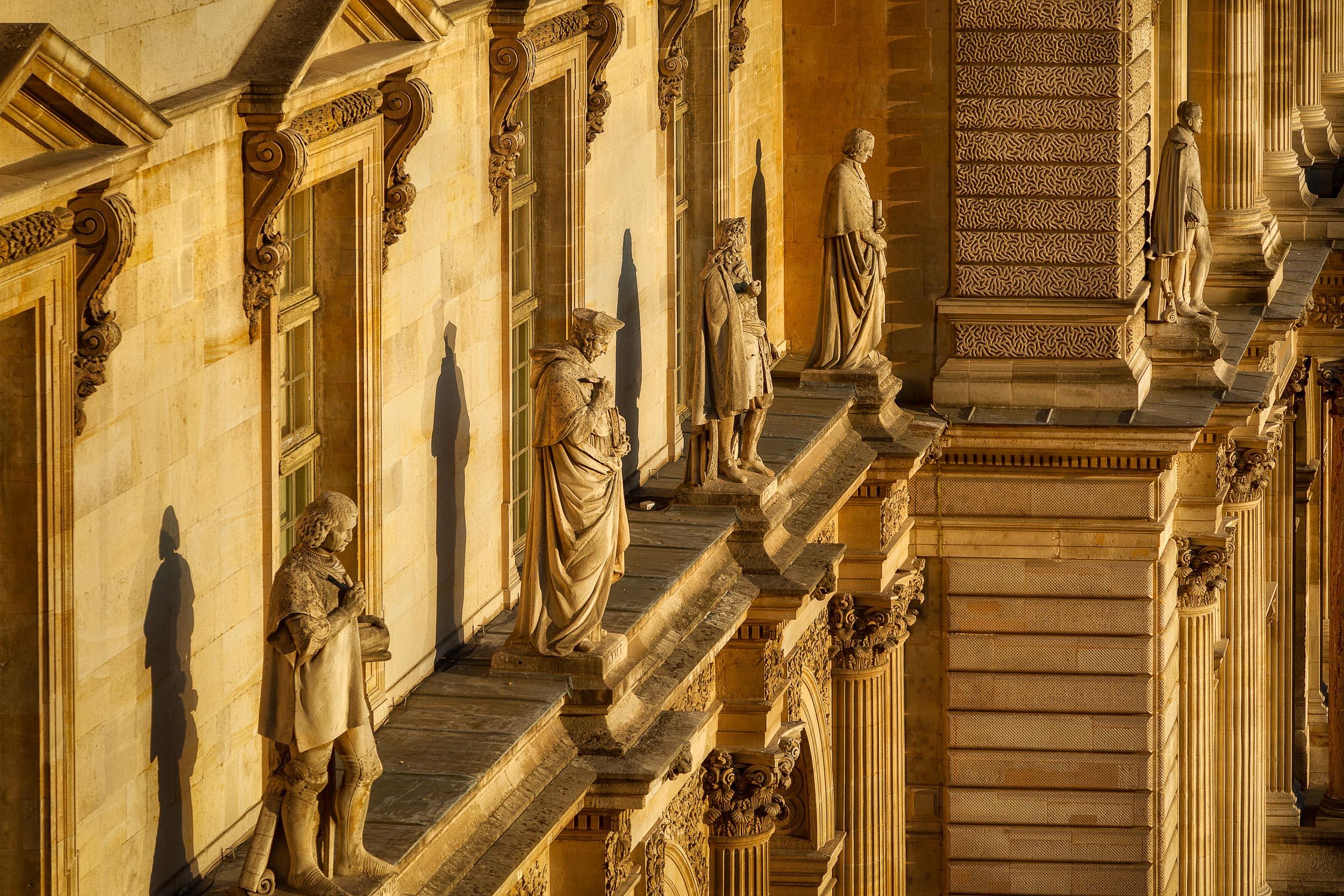 Late afternoon light bathes statues atop the Musée du Louvre in Paris, France.