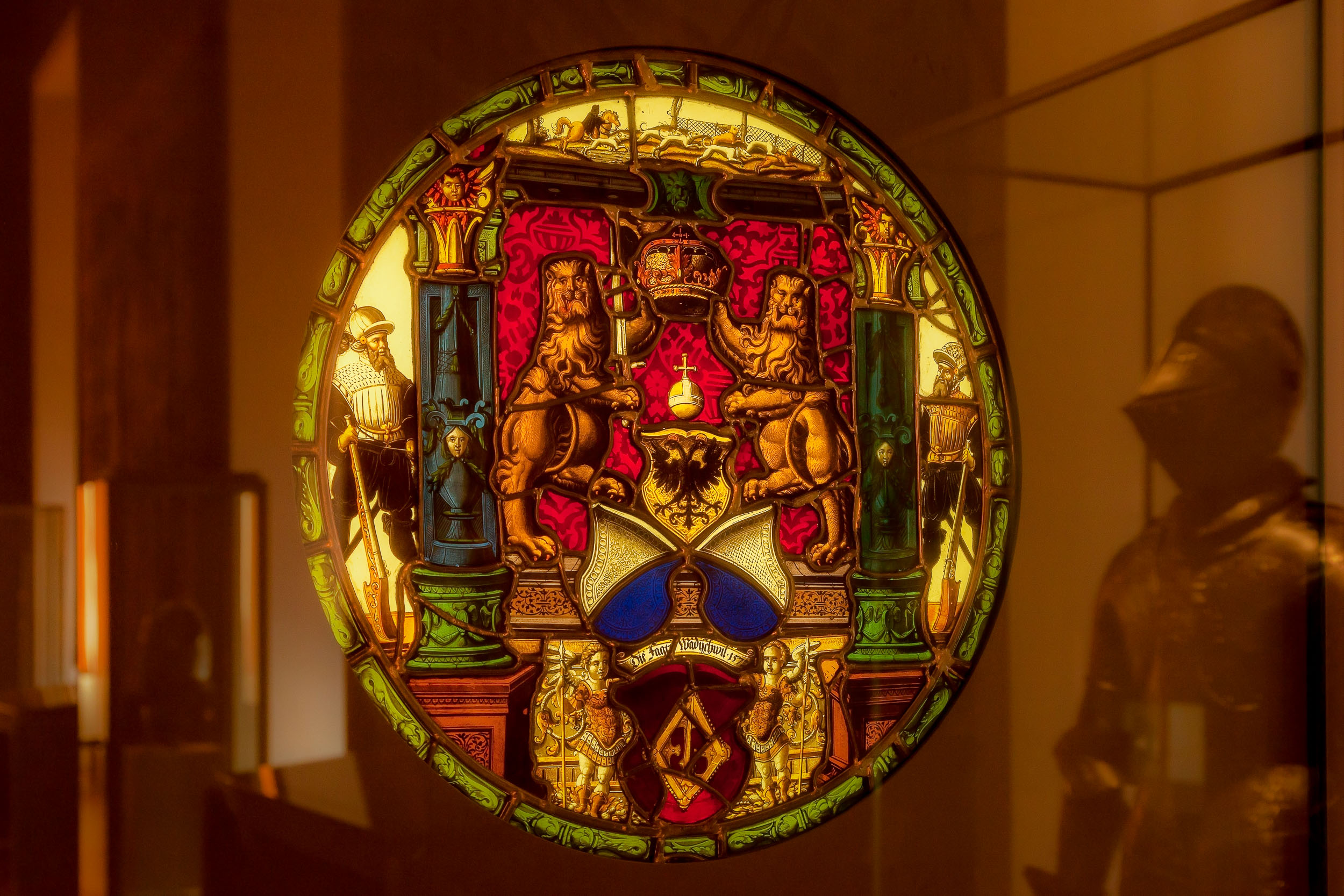 A coat of arms . behind a class cabinet, in the Musée du Louvre in Paris, France .