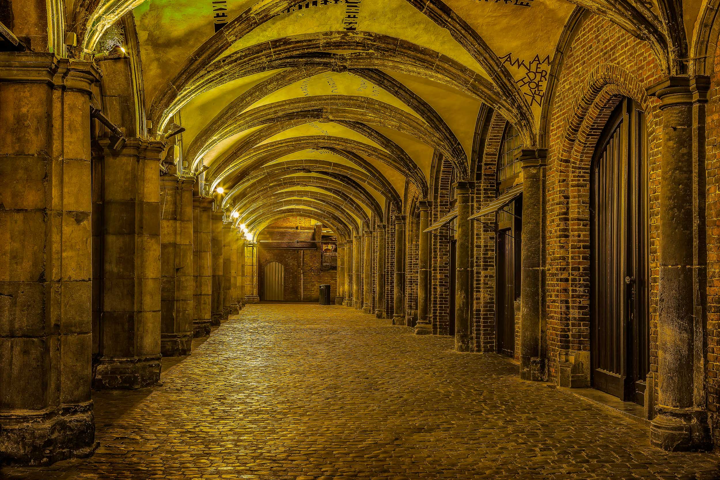 Artificial light illuminates this brooding walkway at night in the city of Bruges (i.e., Brugge), Belgium.