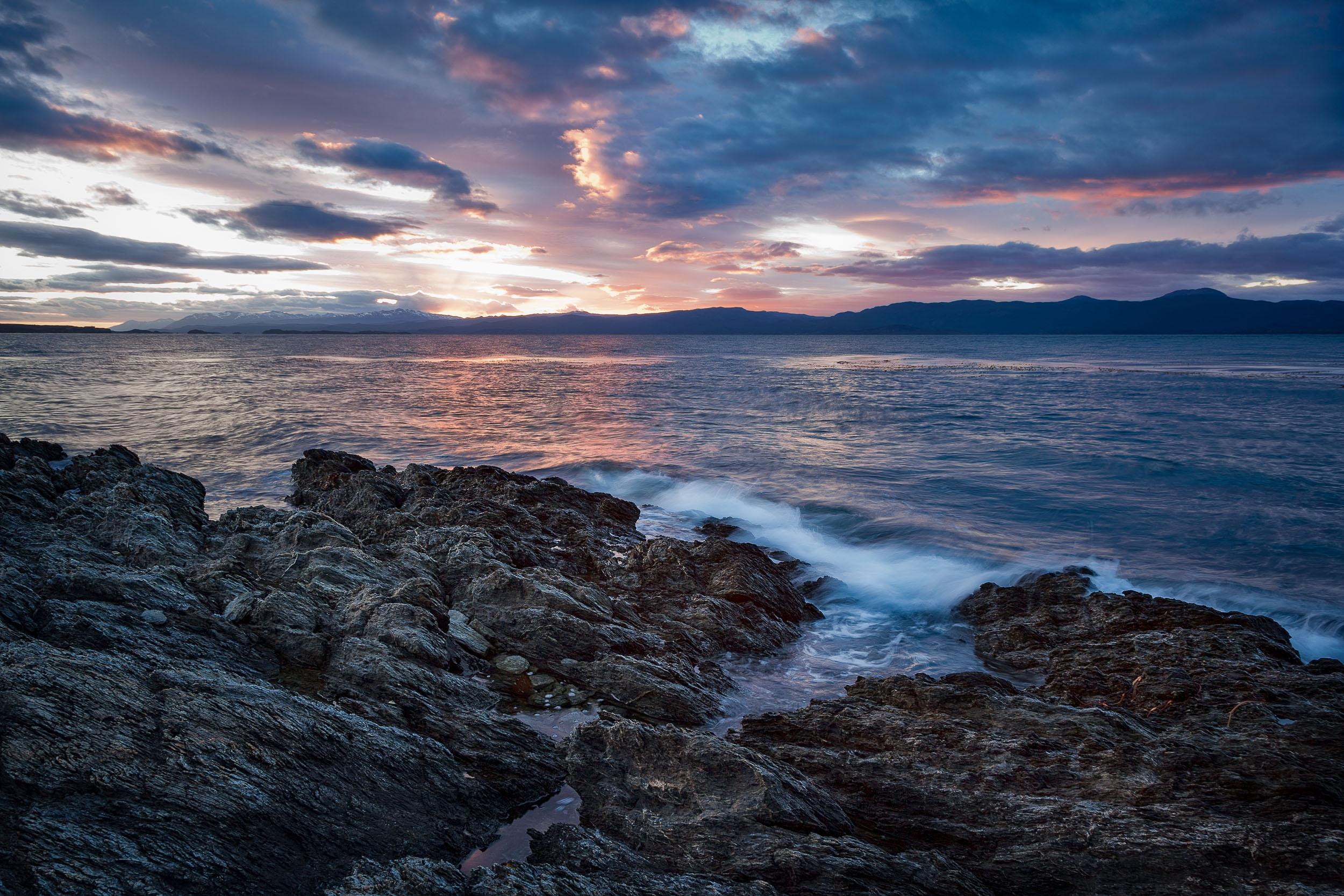 Waves crashing on rocks    at    sunrise    near    Ushuaia    in    Southern Argentina  .