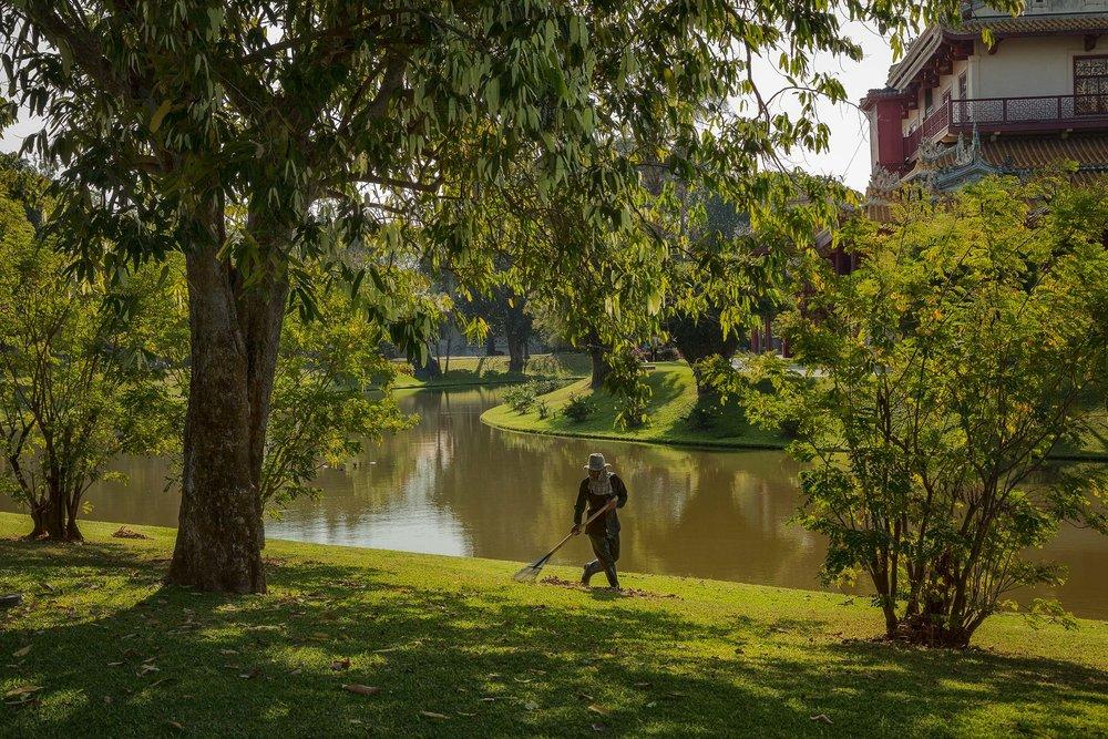 Un travailleur ratisse les pelouses luxuriantes de Bang Pa In près d'Ayutthaya, en Thaïlande.