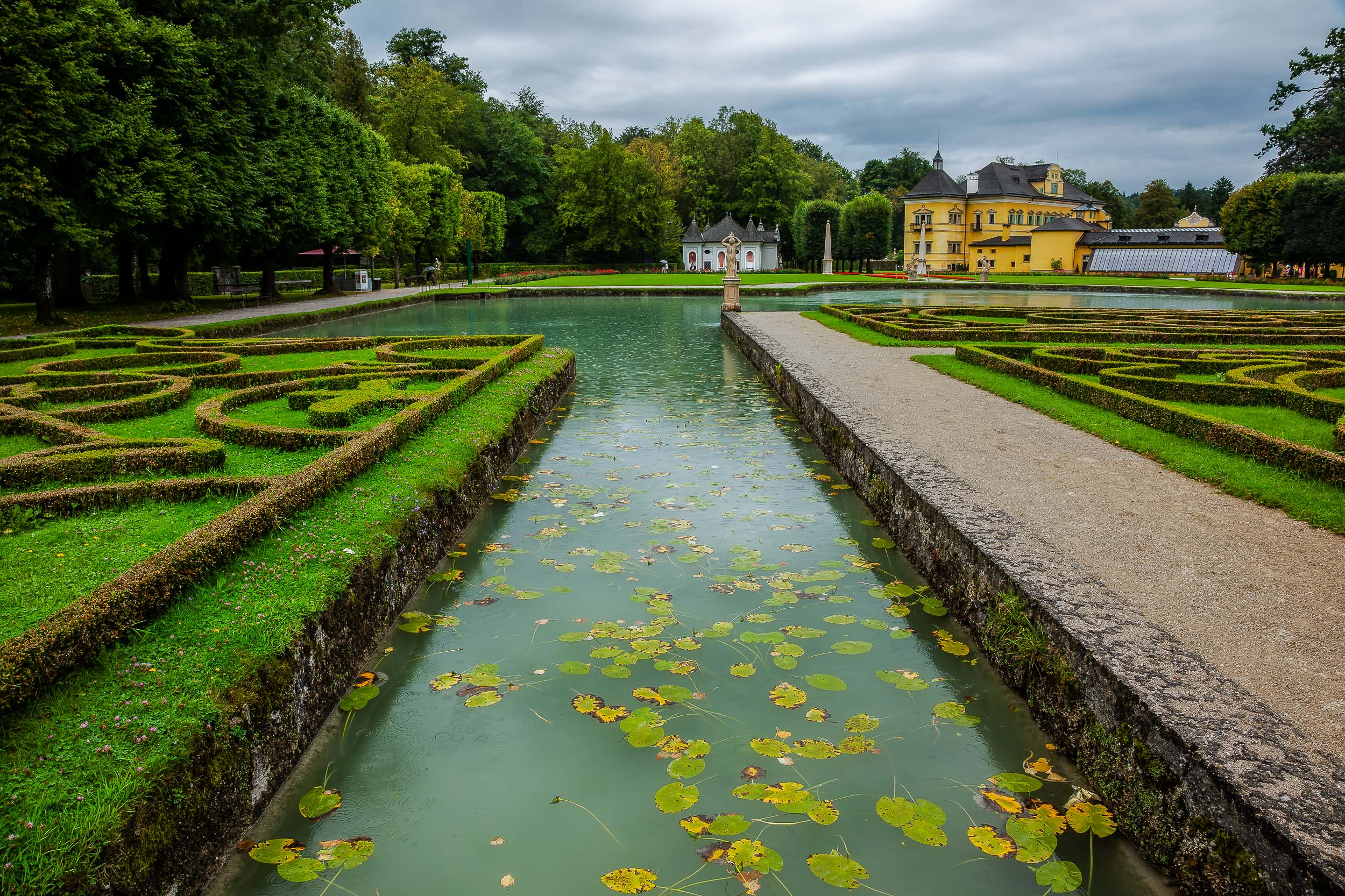 What ever the weather    Salzburg is a beautiful destination    and a wonderful place to explore on foot. This photo showcases    a pool in a beautifully designed garden    where trees and the colors green and yellow dominate.