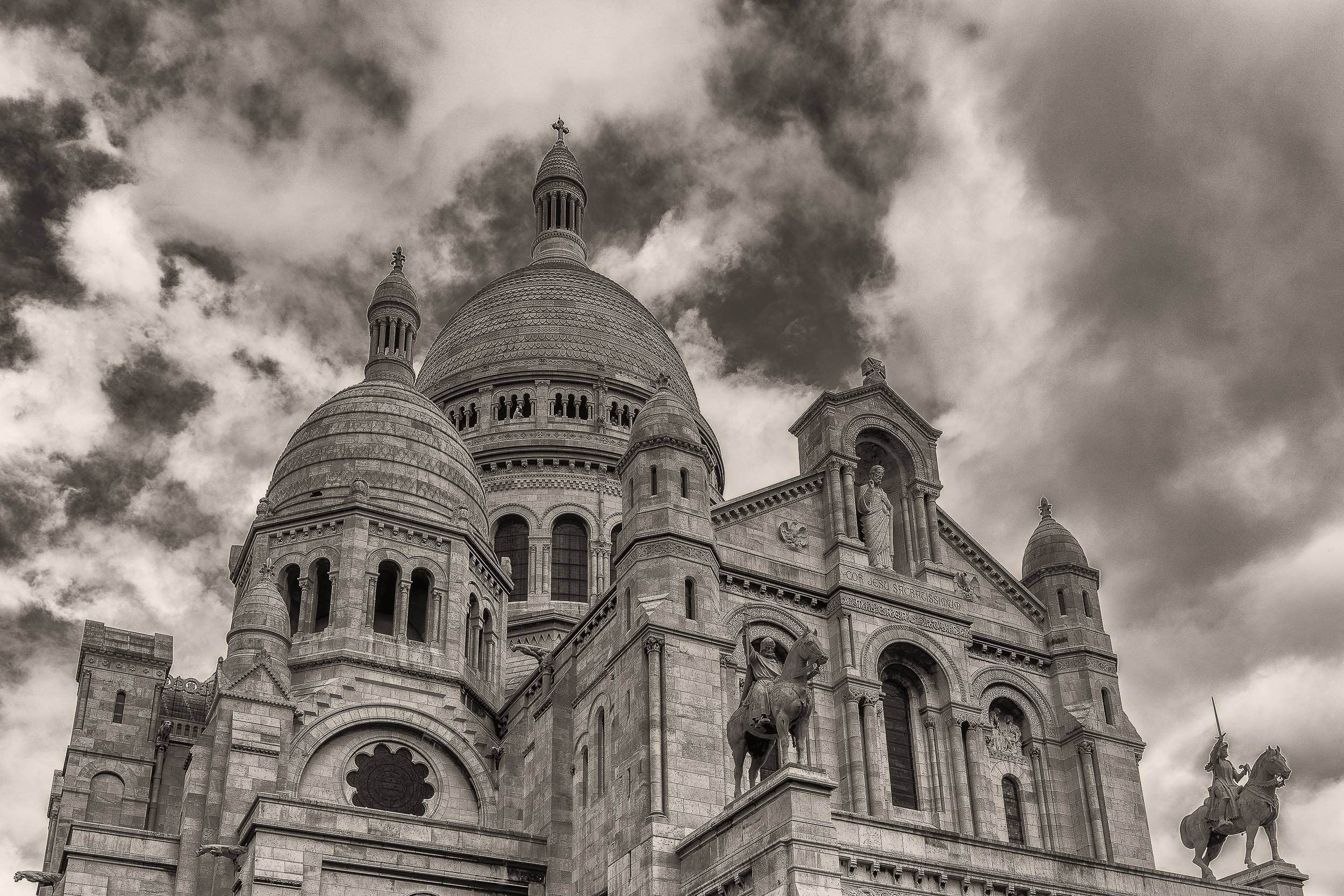 A view up towards the    domes and stautes    that feature so dominantly on the exterior of the    Sacre Coeur Basilica    in    Paris, France   .