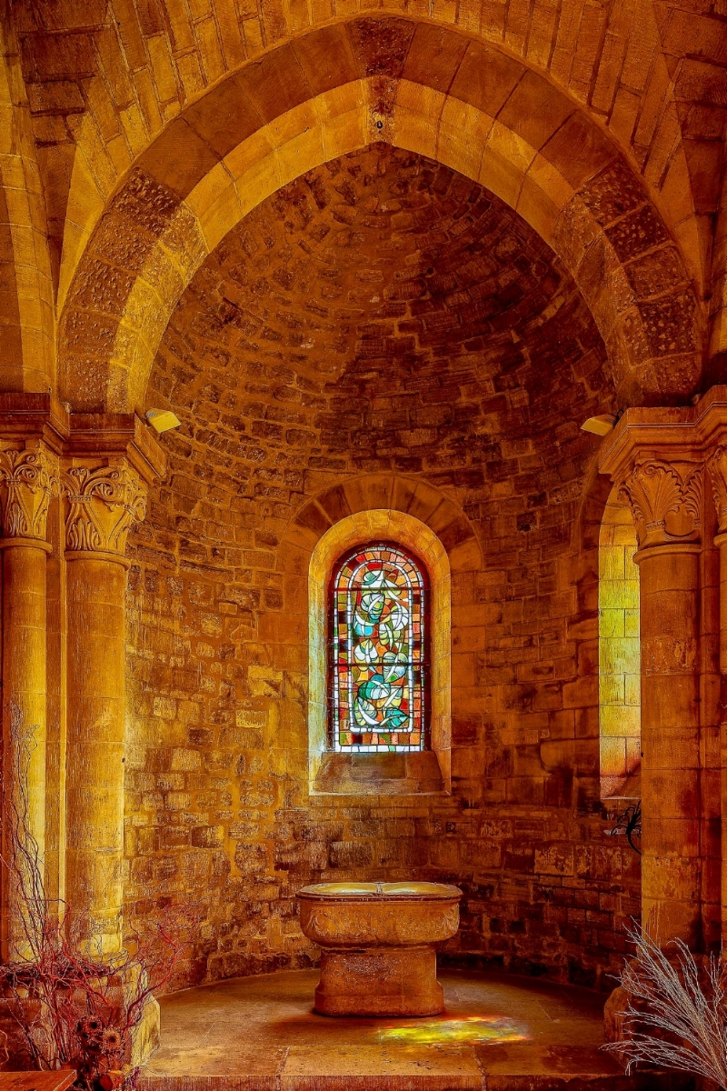 Light shines threw a    stained glass window    and adds    streaks of color    to the    stone floor    of a chapel in    Paris, France   .