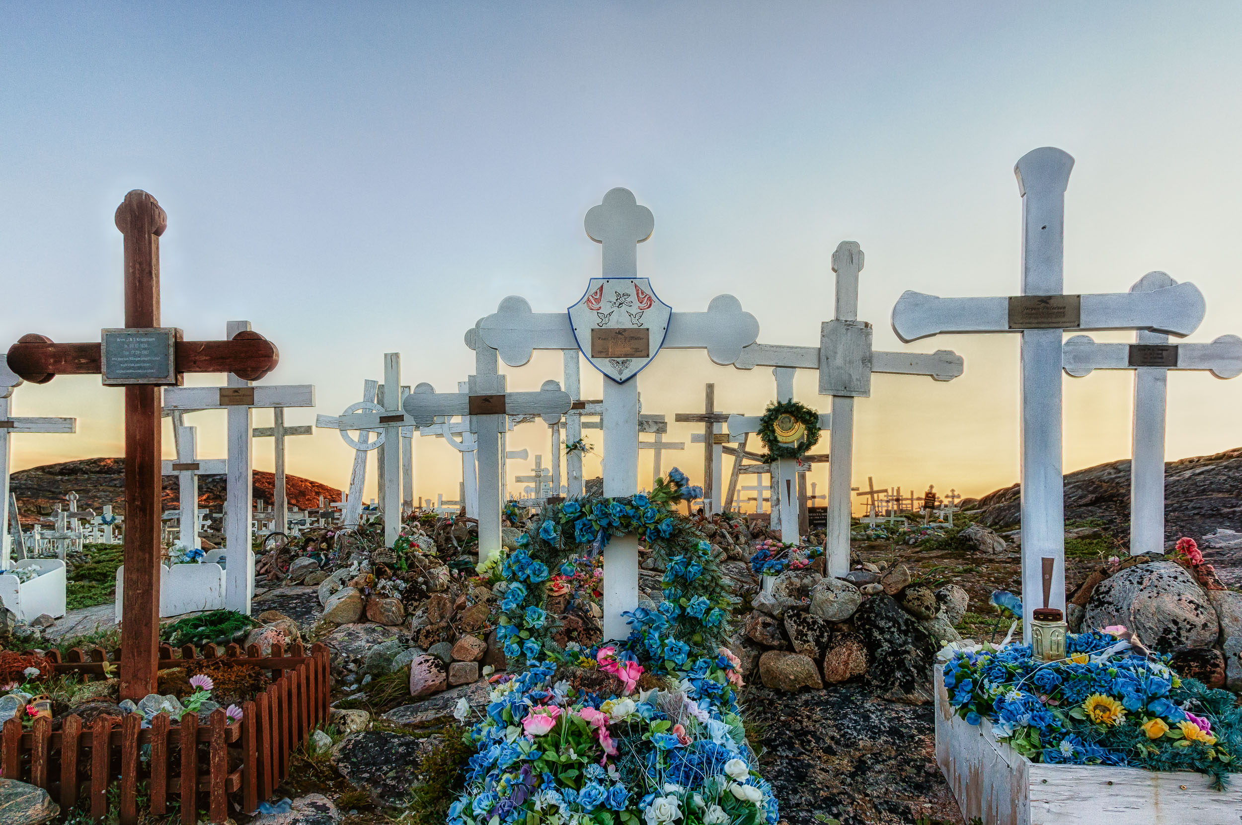 Graves, adorned with flowers   , under the    midnight sun    in    Ilulissat, Greenland   .