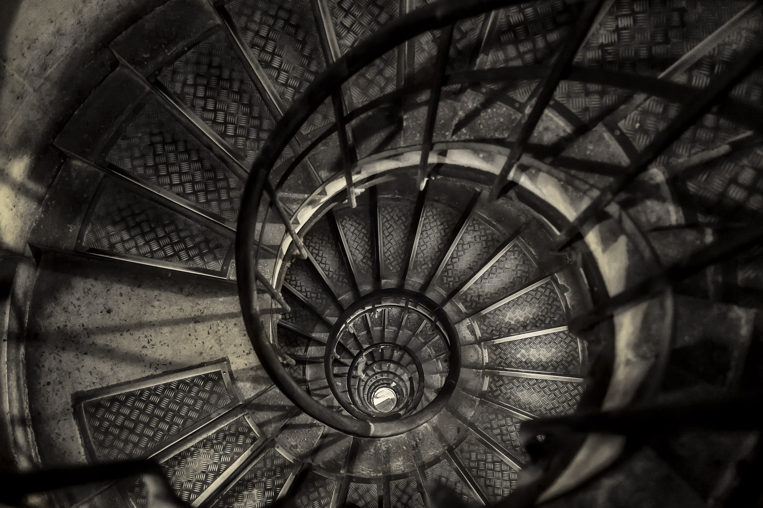 A  moody, birdseye view  looking down a  narrow stairwell  at the  Arc de Triomphe  in  Paris, France .
