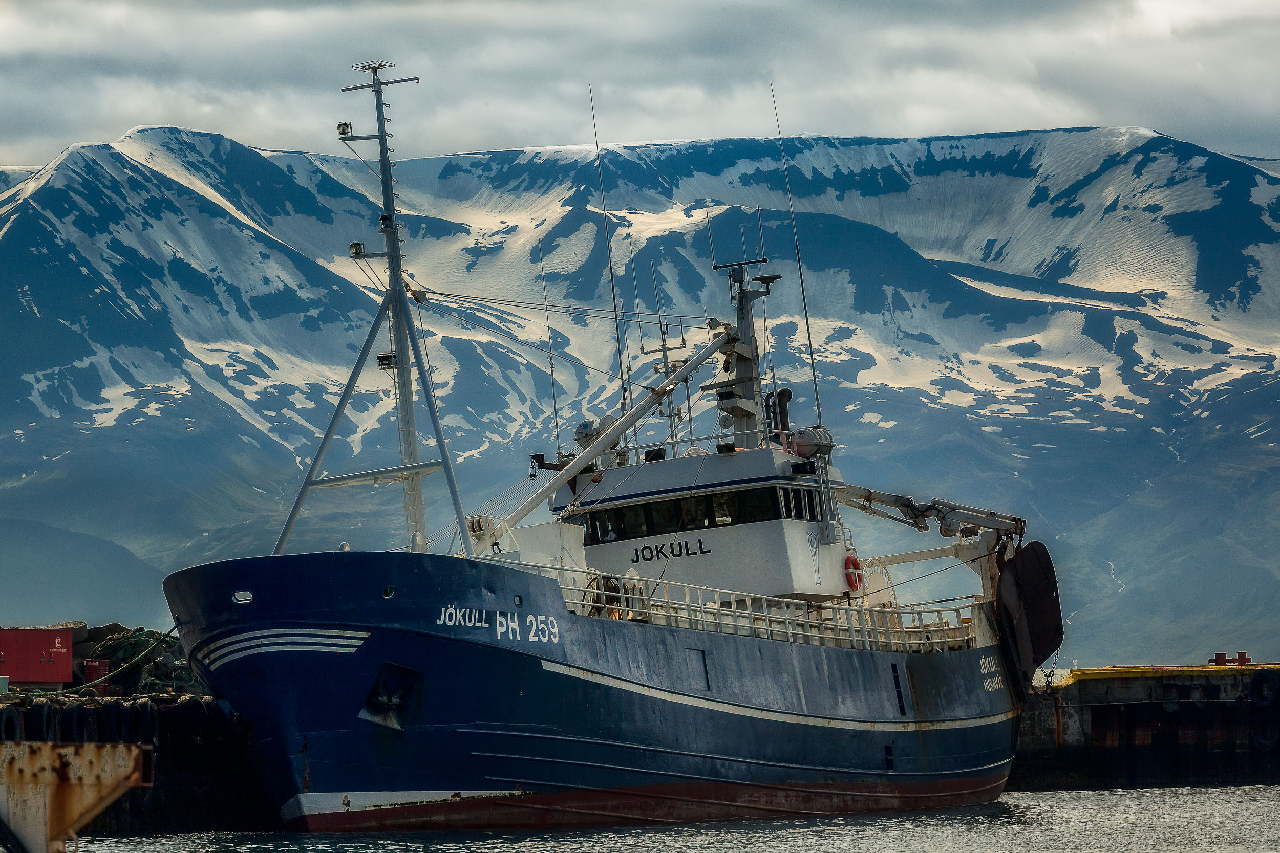 A    fishing boat    in front of distant mountains in    Húsavík, Iceland   .