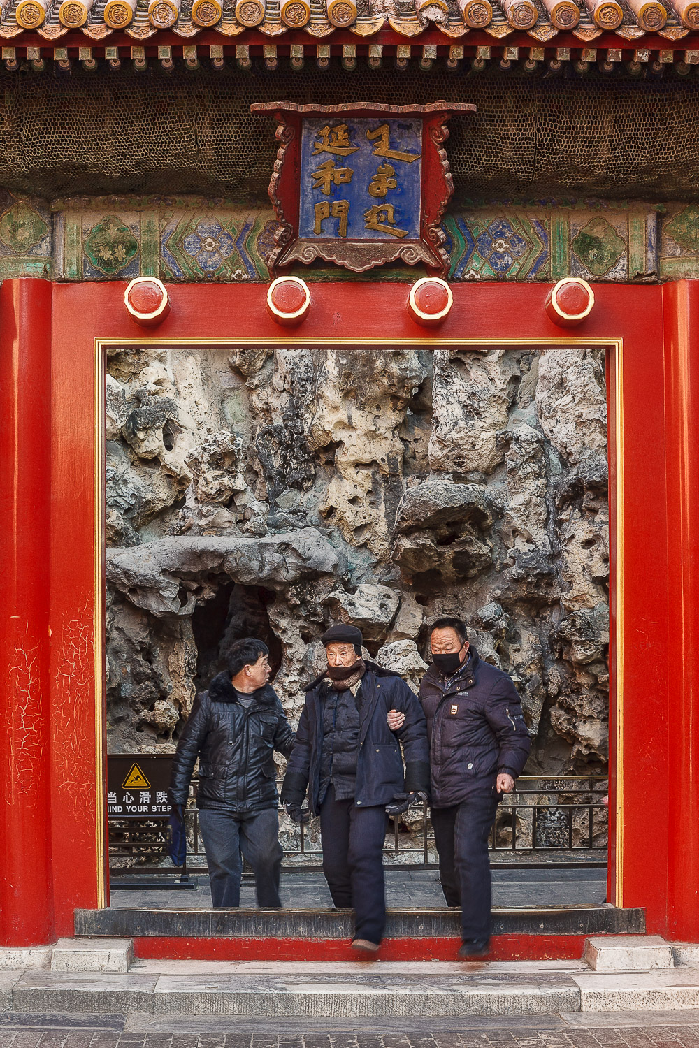 Three men  stepping through an inner gate within the  Forbidden City  in  Beijing, China .