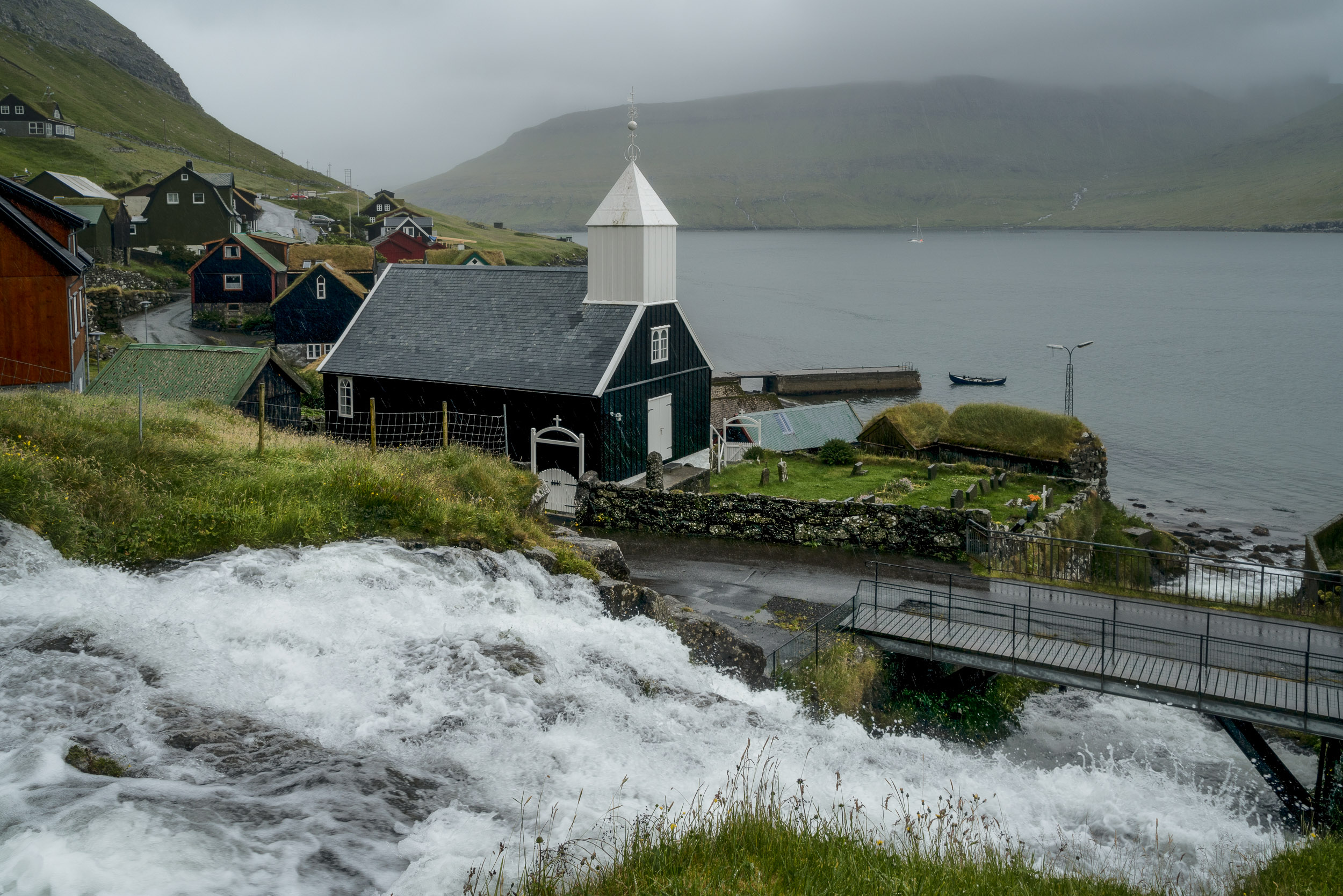 A    waterfall cascades past a church    and into the sea in the    village of Bøur    on    Vagar    in the    Faroe Islands   .