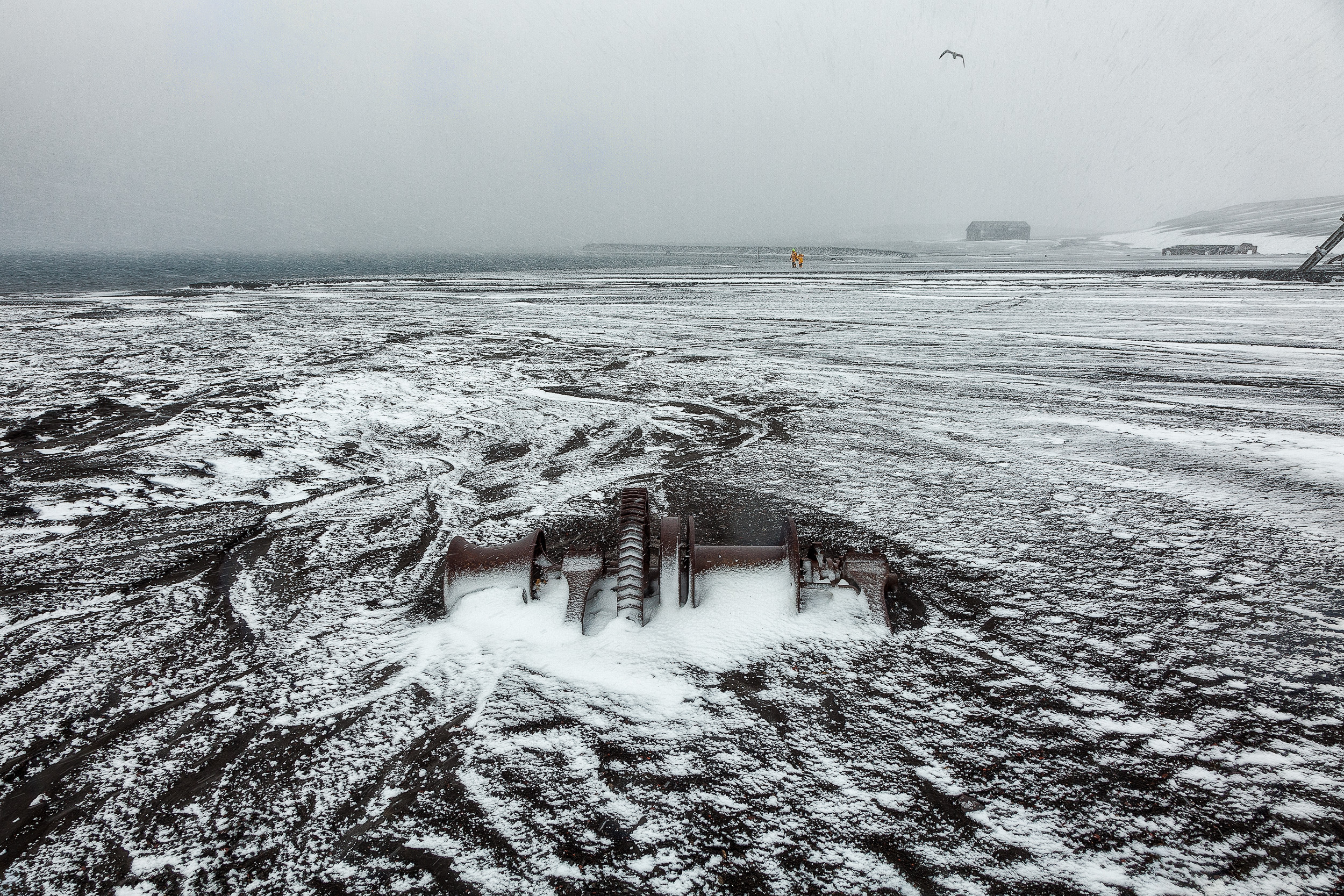 A    heavy snowstorm    sweeps over    Whalers Bay    and    Port Foster    on    Deception Island    in    Antarctica   .