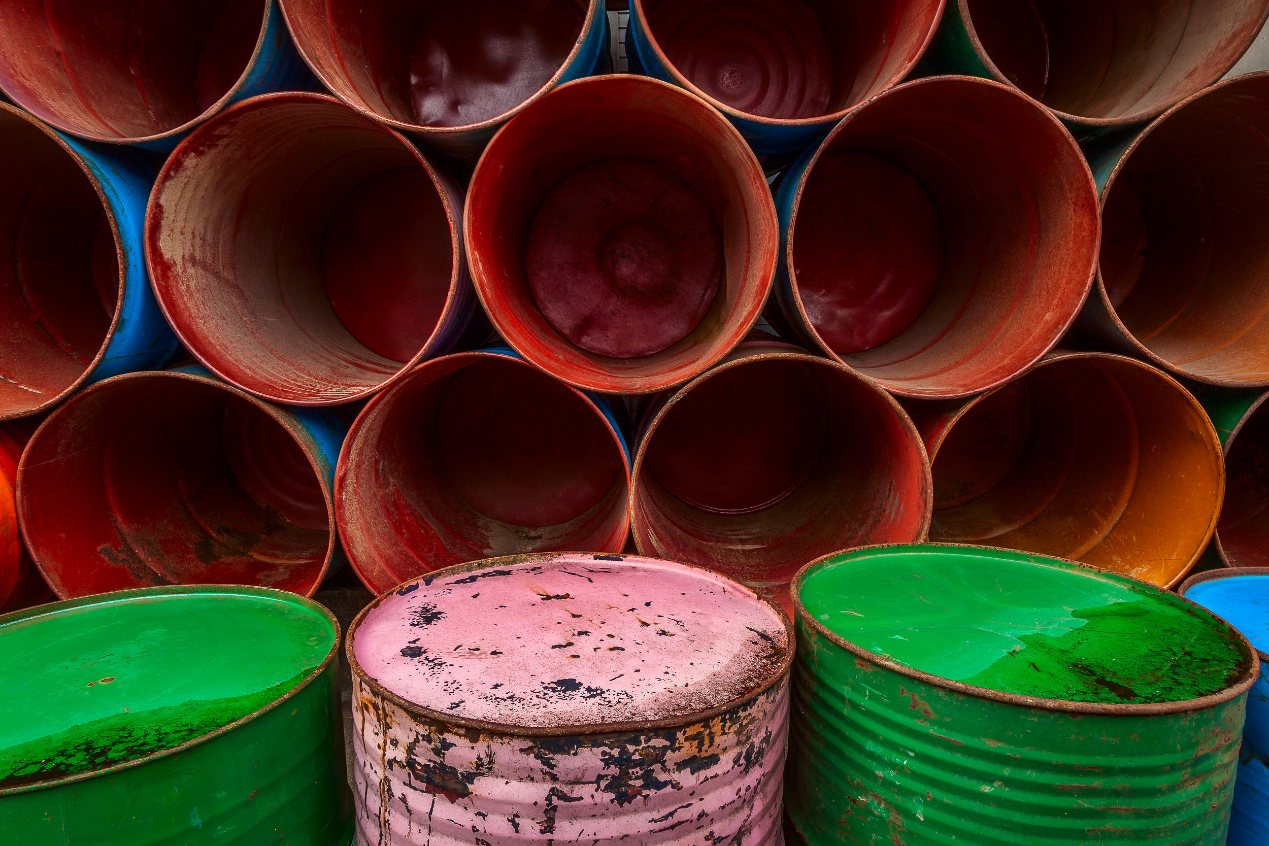 An arrangement of colorful barrels , stacked by the side of the road in Ubud, Bali make for a vivid, symmetrical and well balanced composition.
